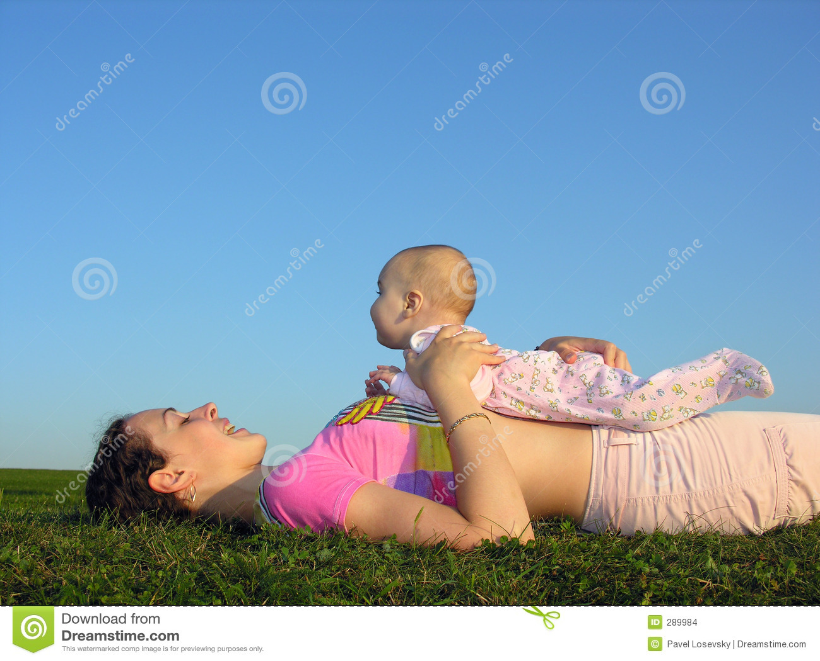 Madre con el bebé en mentira de la puesta del sol