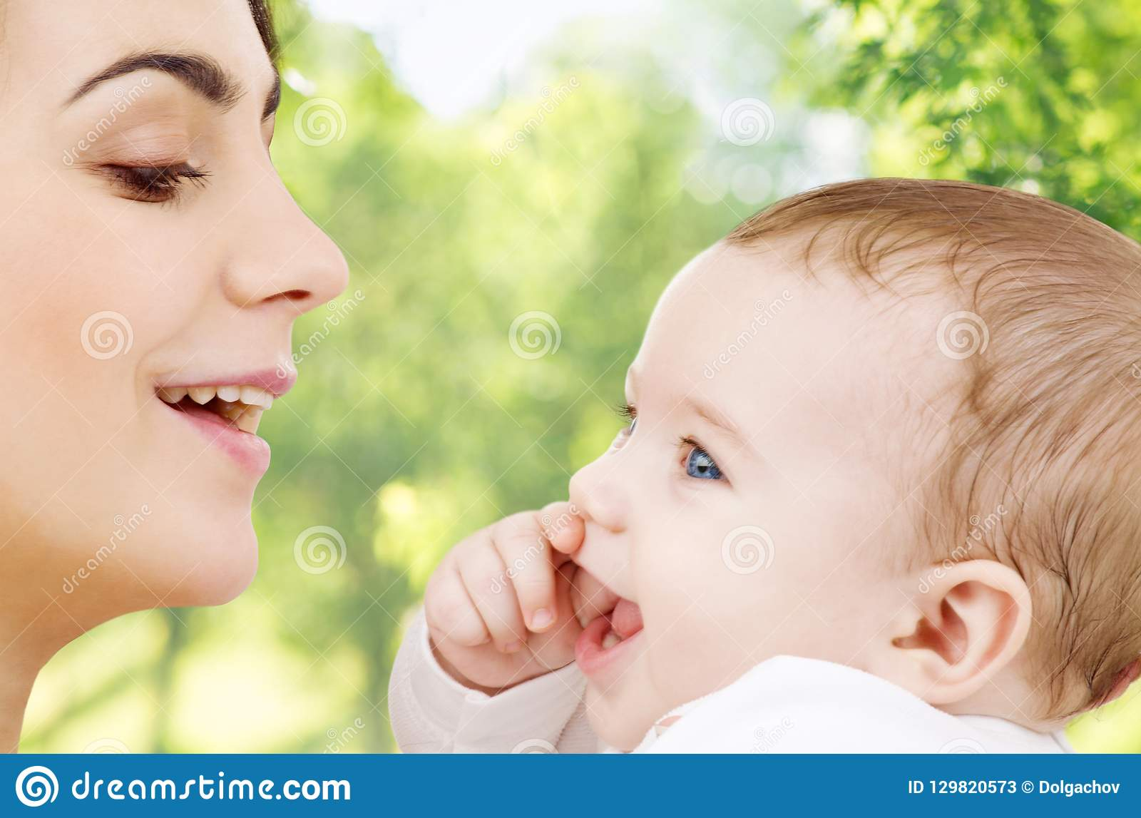 Madre con el bebé sobre fondo natural verde