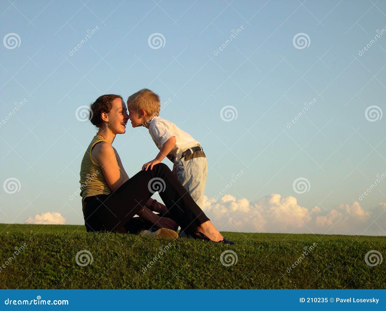 Madre con el hijo en beso del ocaso por la nariz