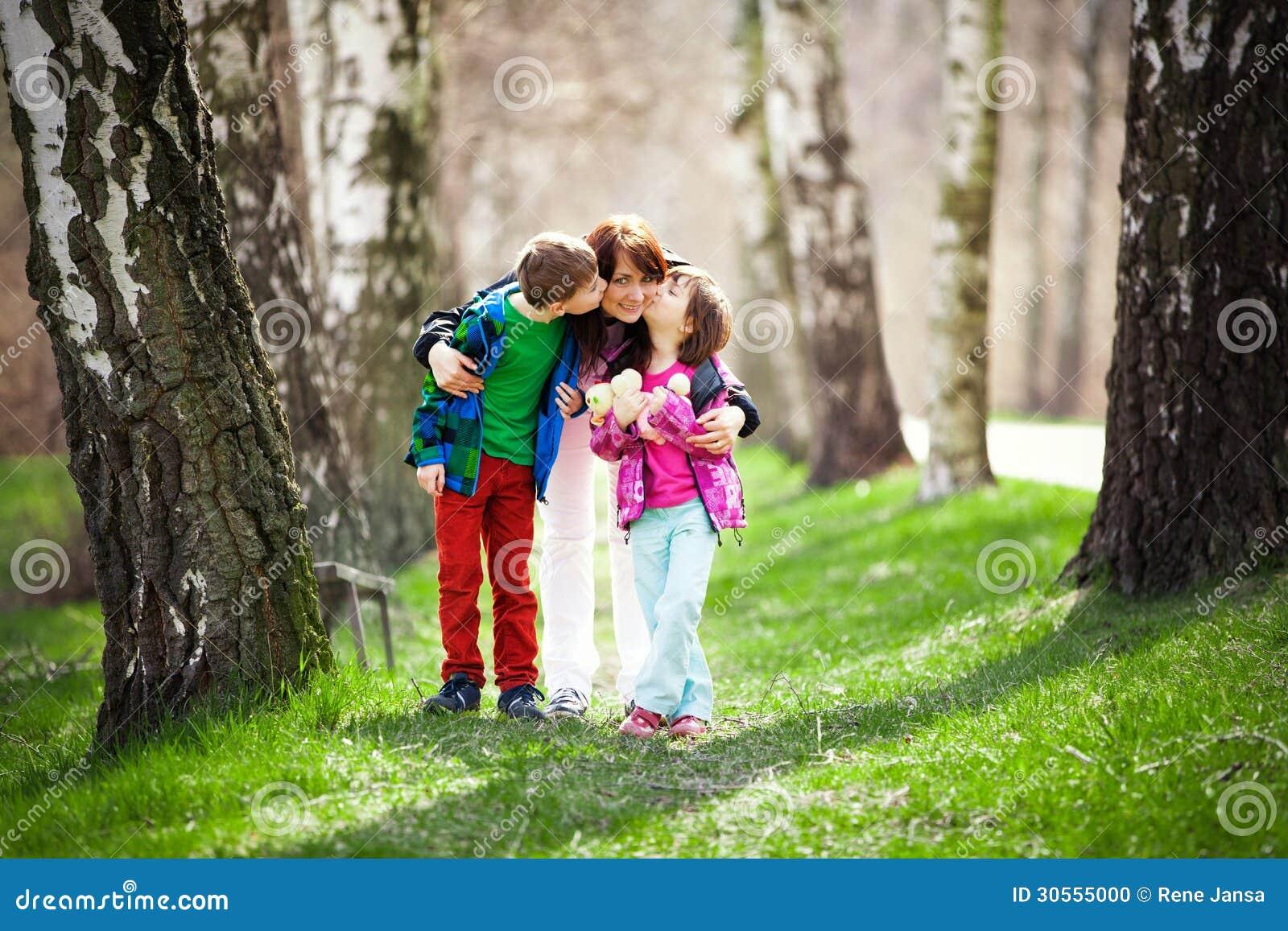 Madre con el hijo y la hija en bosque