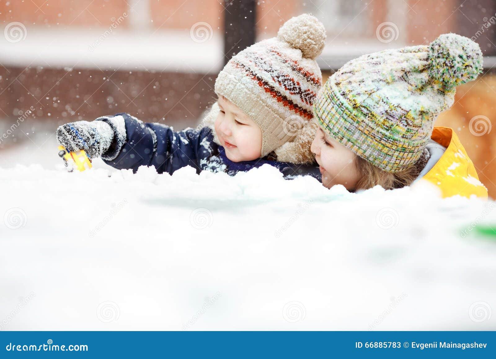 Madre con el juego de niños en nieve en el paseo del invierno, emociones positivas, al aire libre Nevadas, ventisca