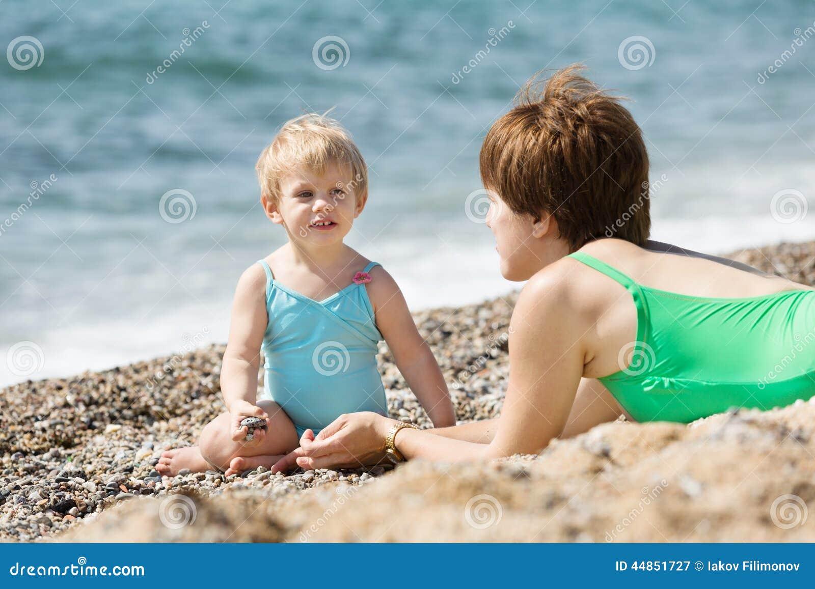 Madre con el niño adorable en la playa de la arena
