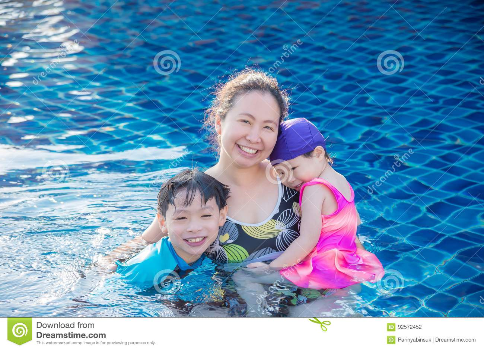 Madre con i suoi bambini nella piscina
