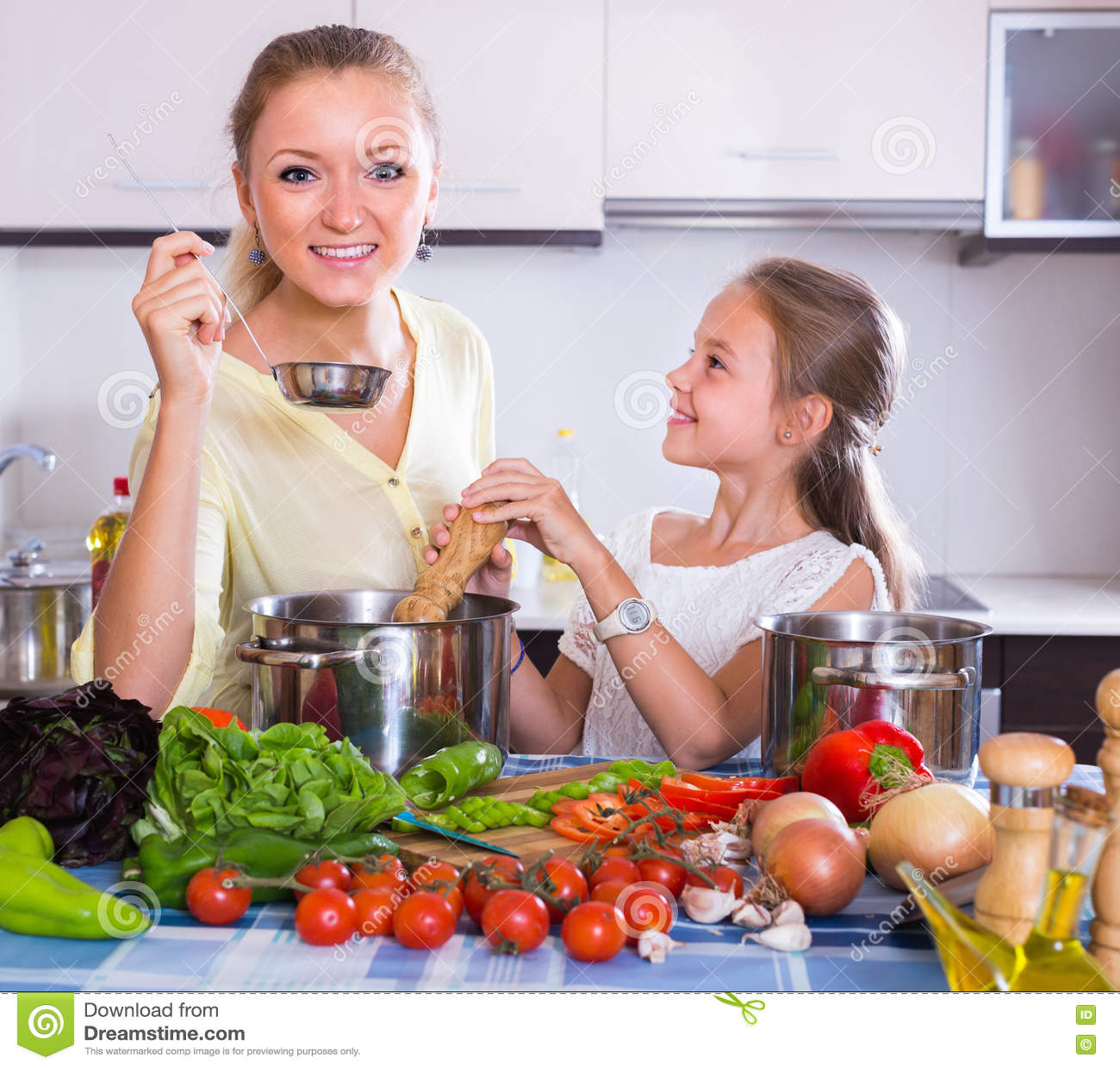 Madre con la hija que cocina los veggies