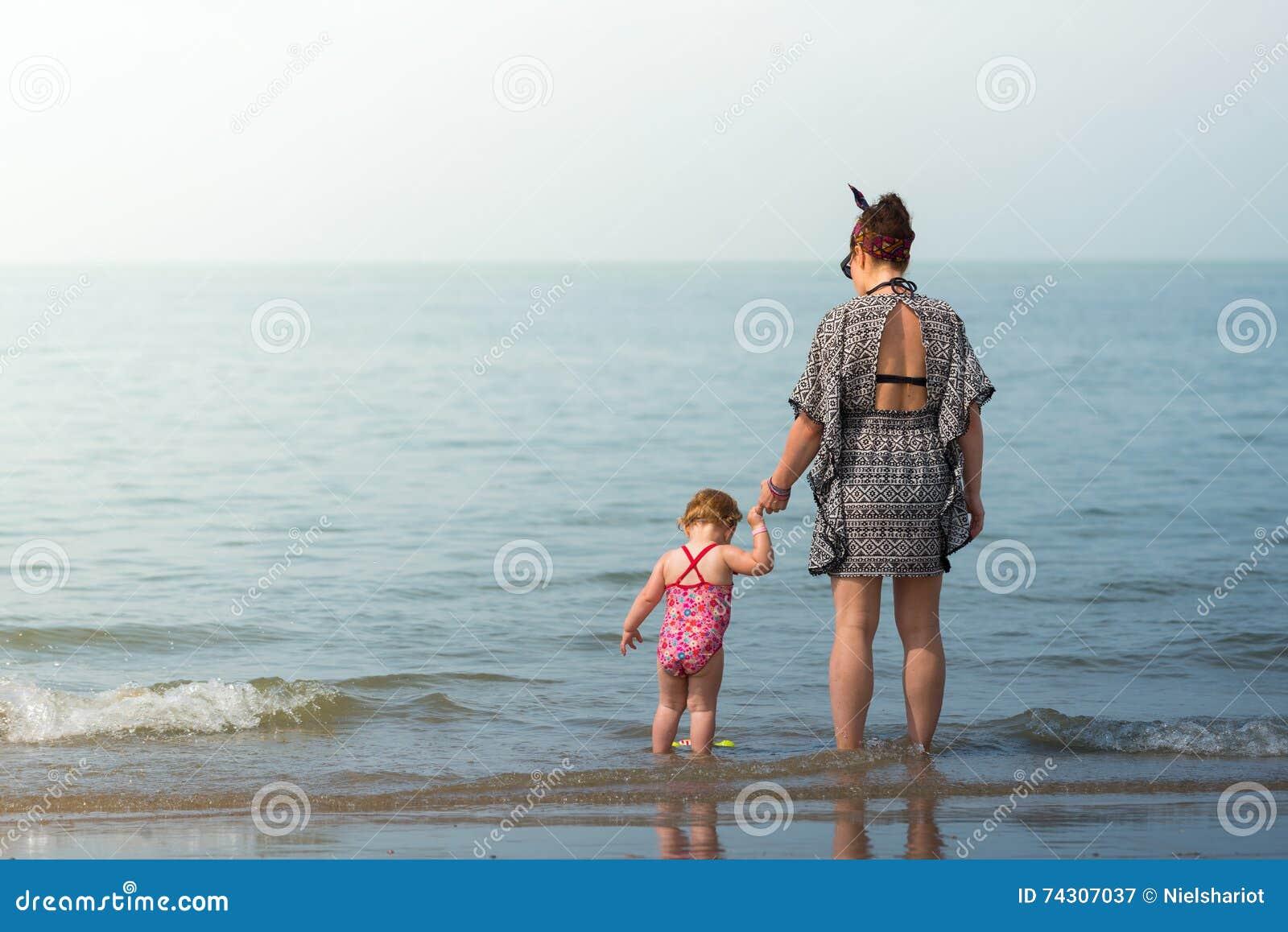Madre con la neonata sulla spiaggia