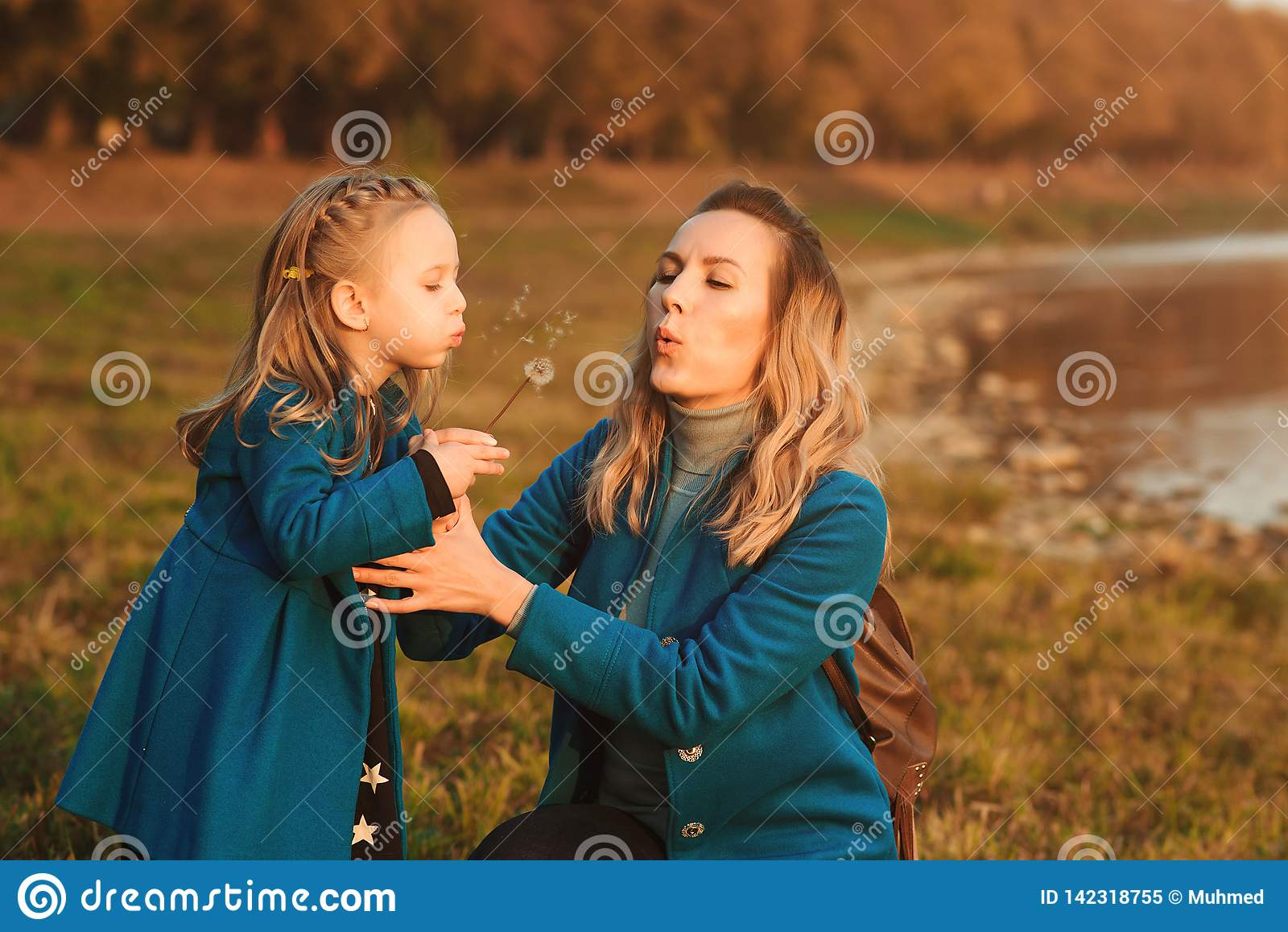 Madre con la pequeña hija que sopla al diente de león en naturaleza al aire libre Concepto feliz de la familia, de la niñez y