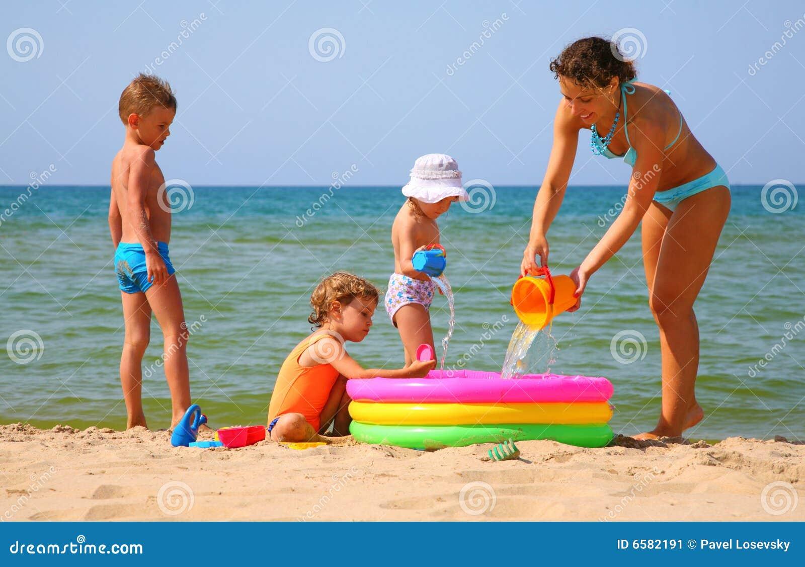 Madre con los niños en el mar y la piscina