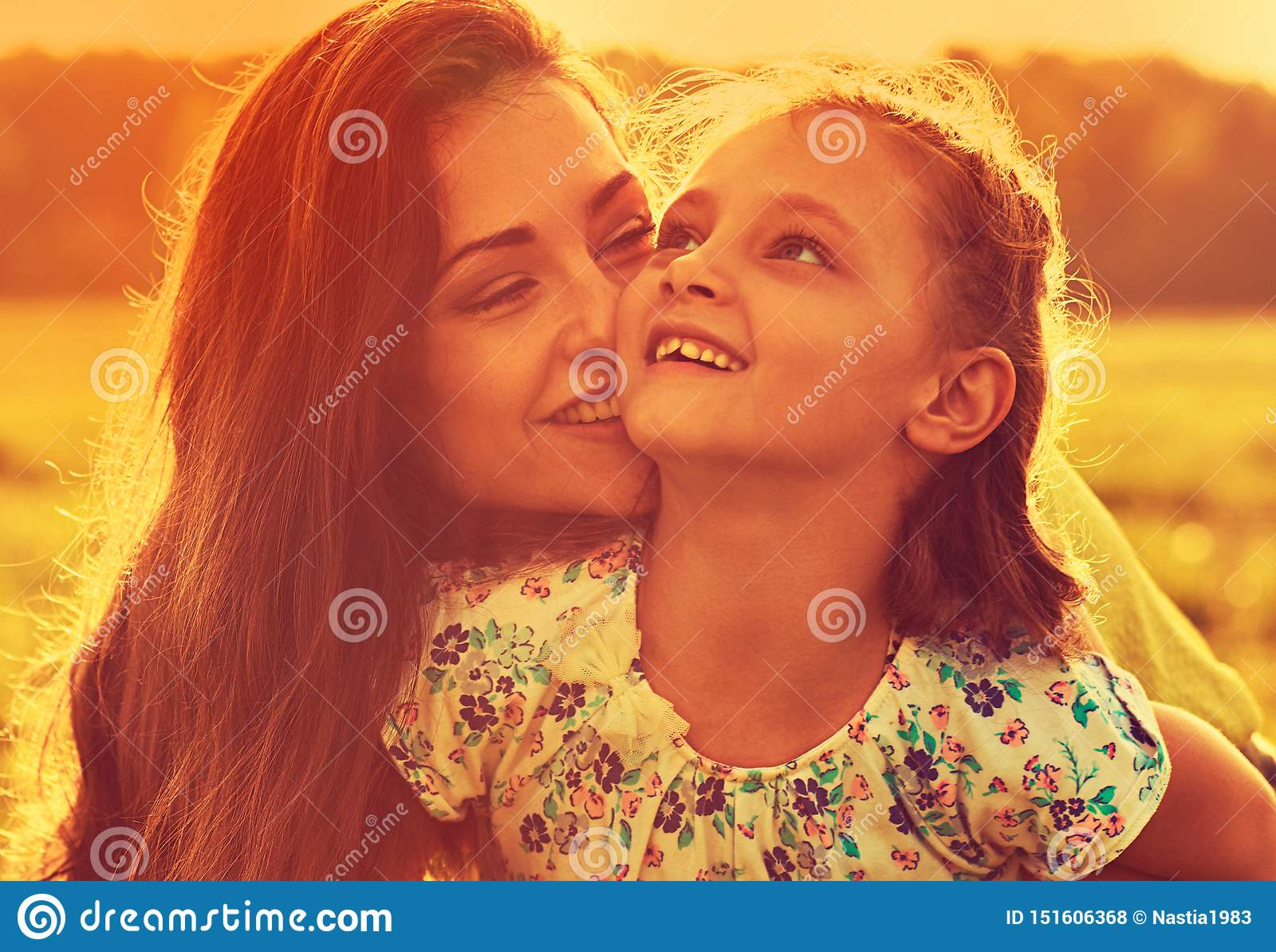 Madre de goce feliz que abraza a su muchacha de risa juguetona del niño en luz soleada de la puesta del sol en fondo del verano p