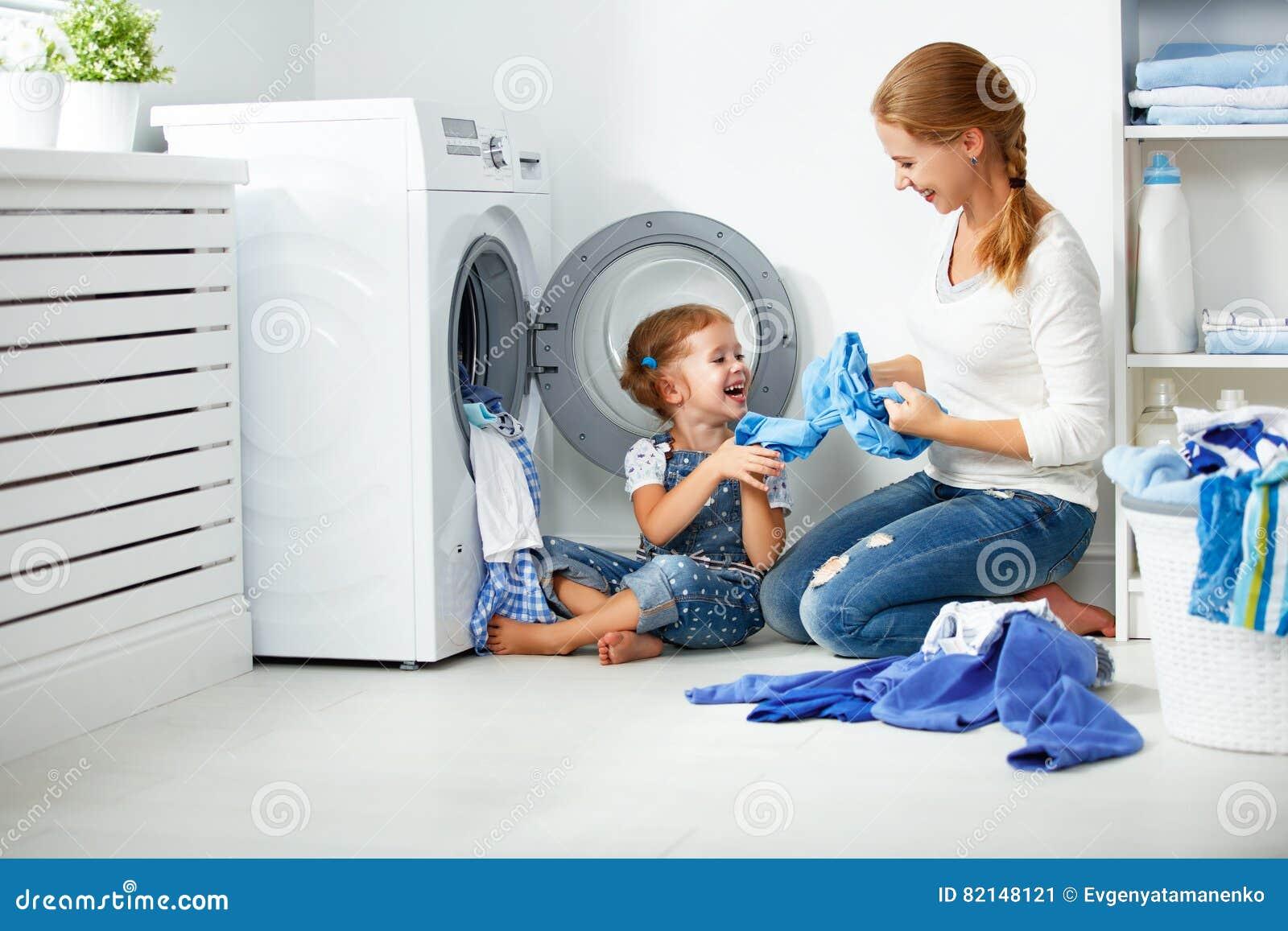 Madre de la familia y ayudante de la muchacha del niño pequeño en lavadero cerca de la lavadora