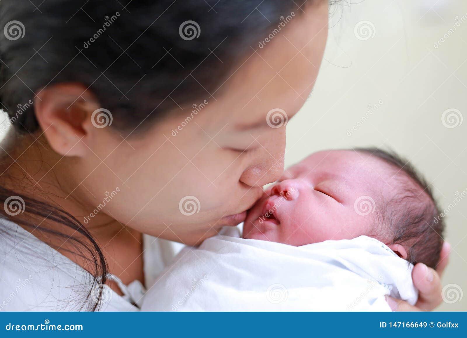 Madre del primer que besa al bebé infantil en sus brazos en hospital después de sitio de entrega