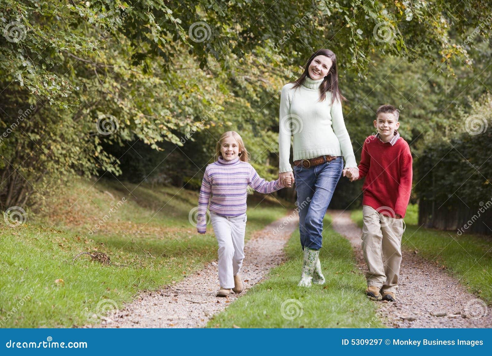 Download Madre E Bambini Che Camminano Lungo Il Percorso Del Terreno Boscoso Immagine Stock - Immagine di cosy, togetherness: 5309297