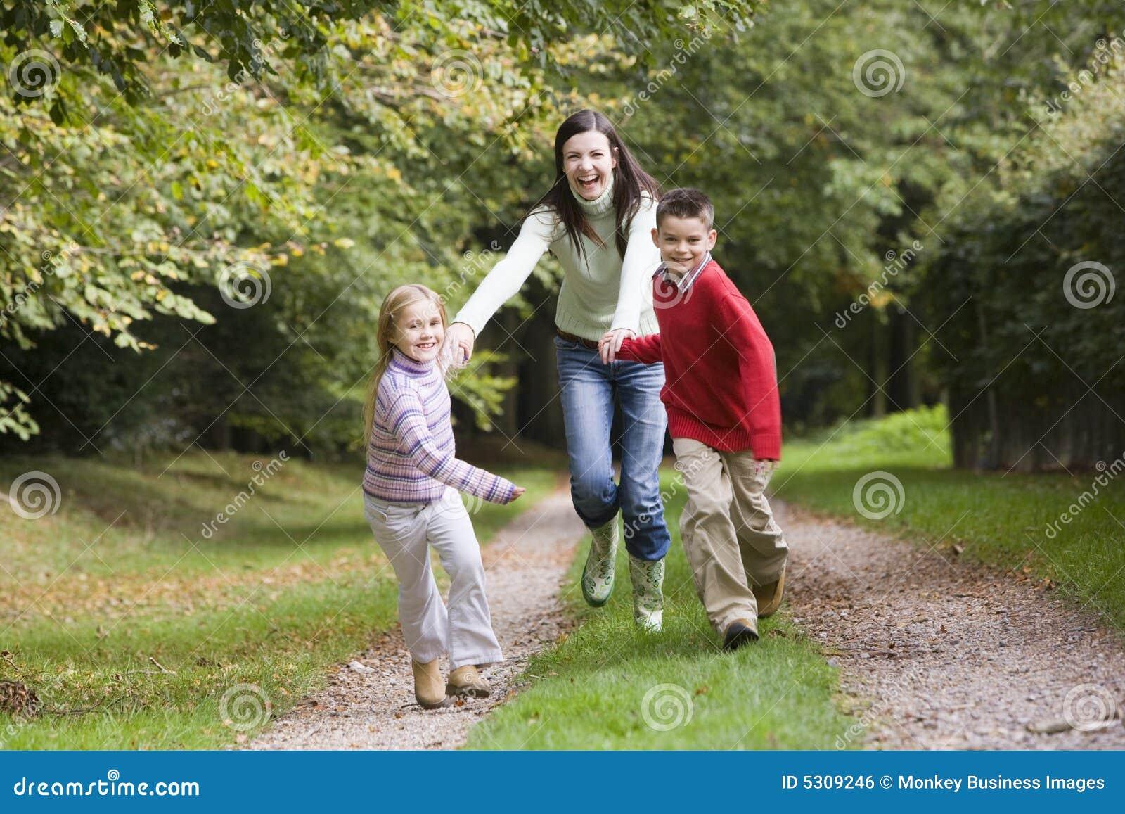 Download Madre E Bambini Che Funzionano Lungo Il Percorso Del Terreno Boscoso Fotografia Stock - Immagine di alberi, lifestyle: 5309246