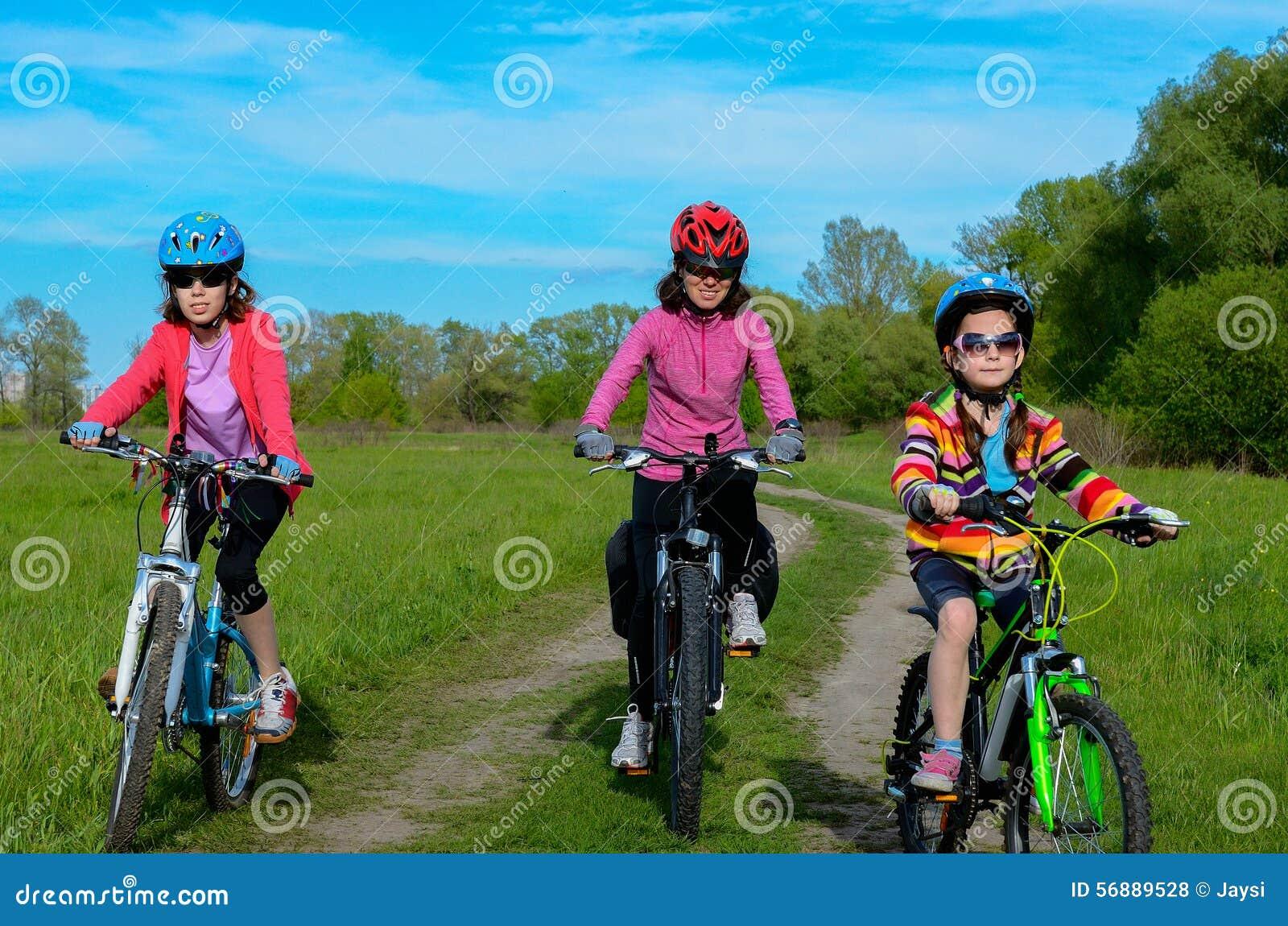 Madre e bambini felici sulle bici che ciclano all aperto