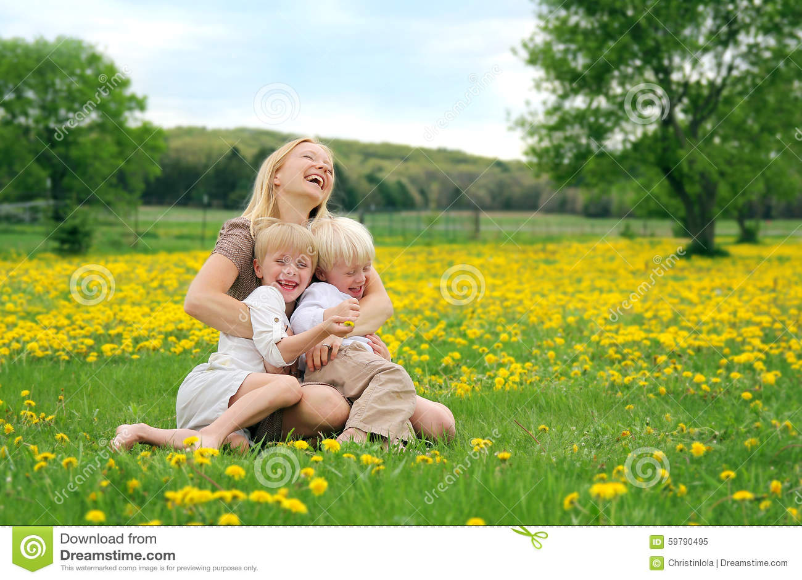 Madre e bambini piccoli che si siedono nella risata del prato del fiore