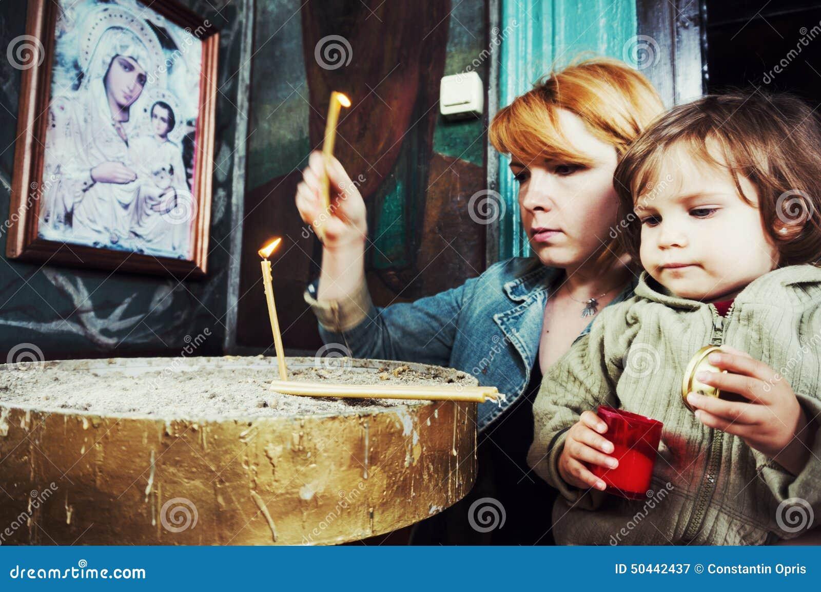 Madre e bambino che accendono le candele in chiesa