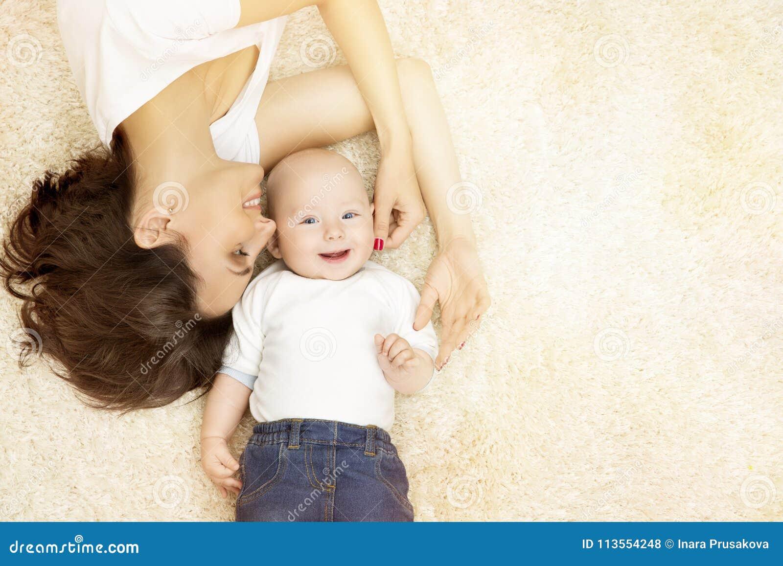 Madre e bambino che si trovano sul tappeto, ritratto felice della famiglia, ragazzo del bambino
