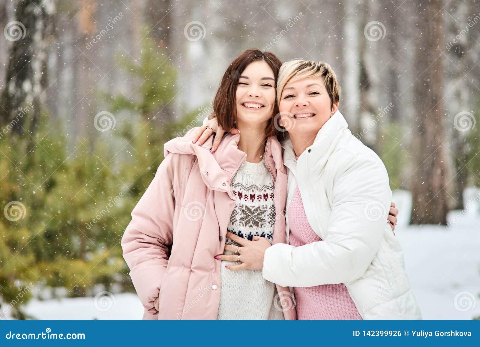 Madre e figlia adulta che camminano in precipitazioni nevose della foresta di inverno