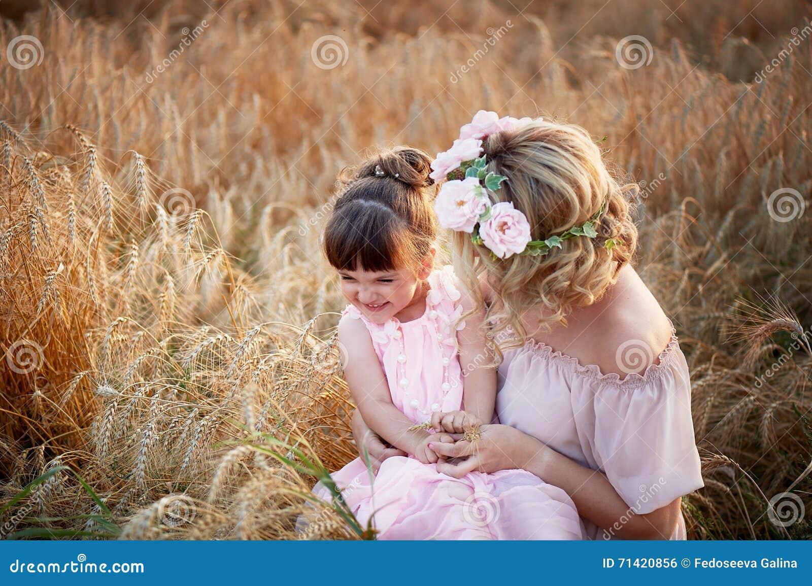 Madre e figlia che abbracciano sulla sua testa una ghirlanda delle rose, immagine morbida