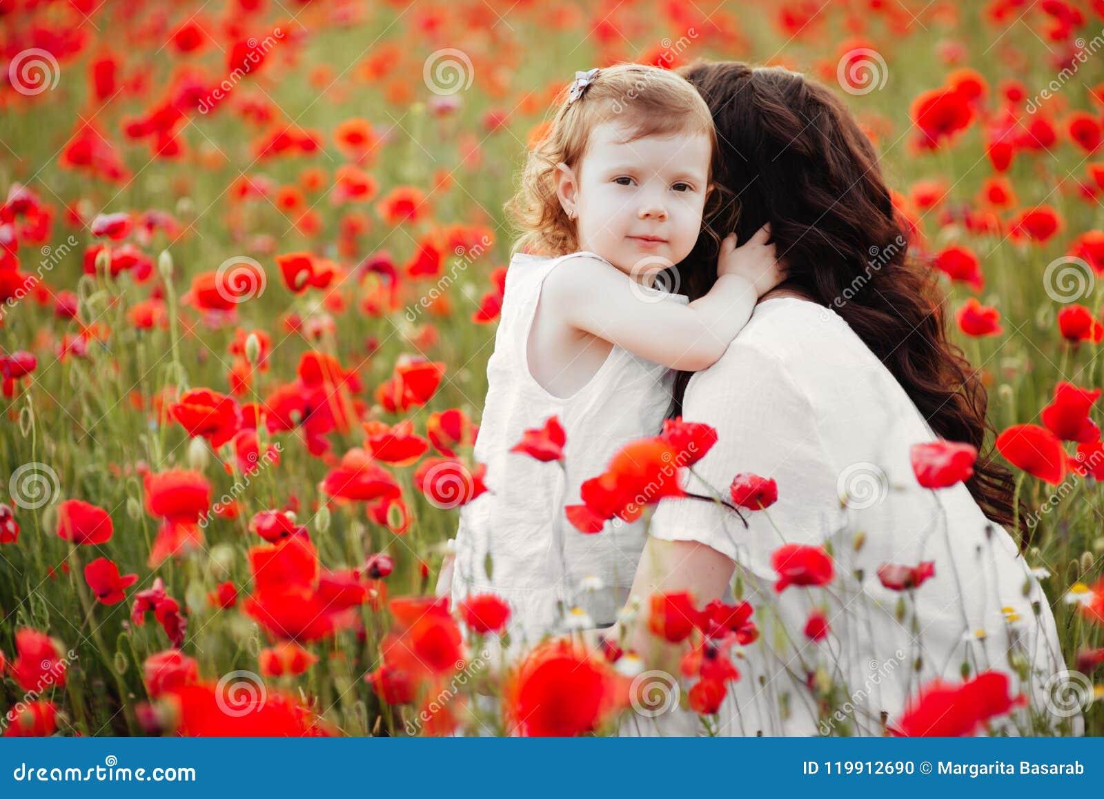 Madre e figlia che giocano nel giacimento di fiore