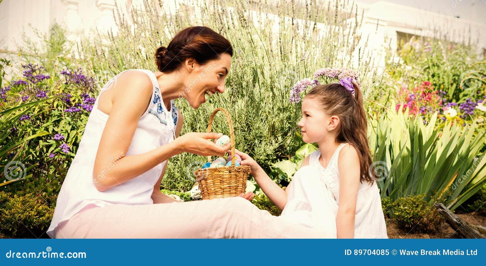Madre e figlia che raccolgono le uova di Pasqua