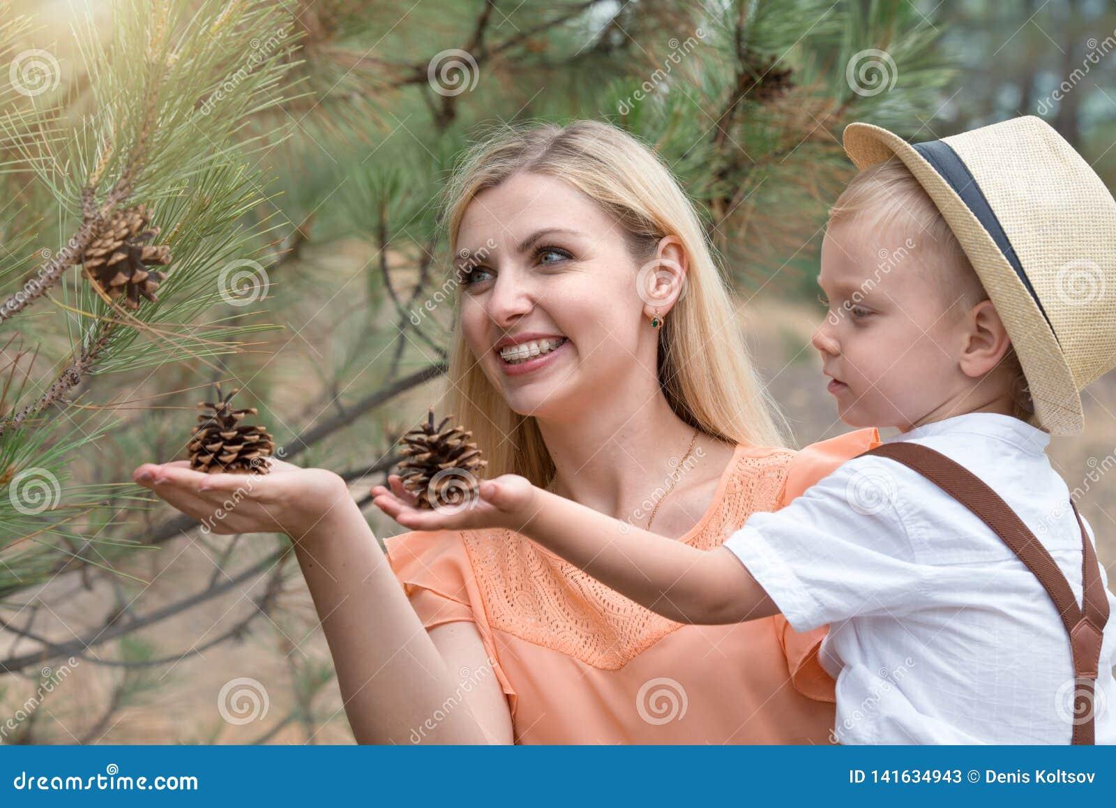 Madre e figlio che raccolgono i coni forestFamily nello svago