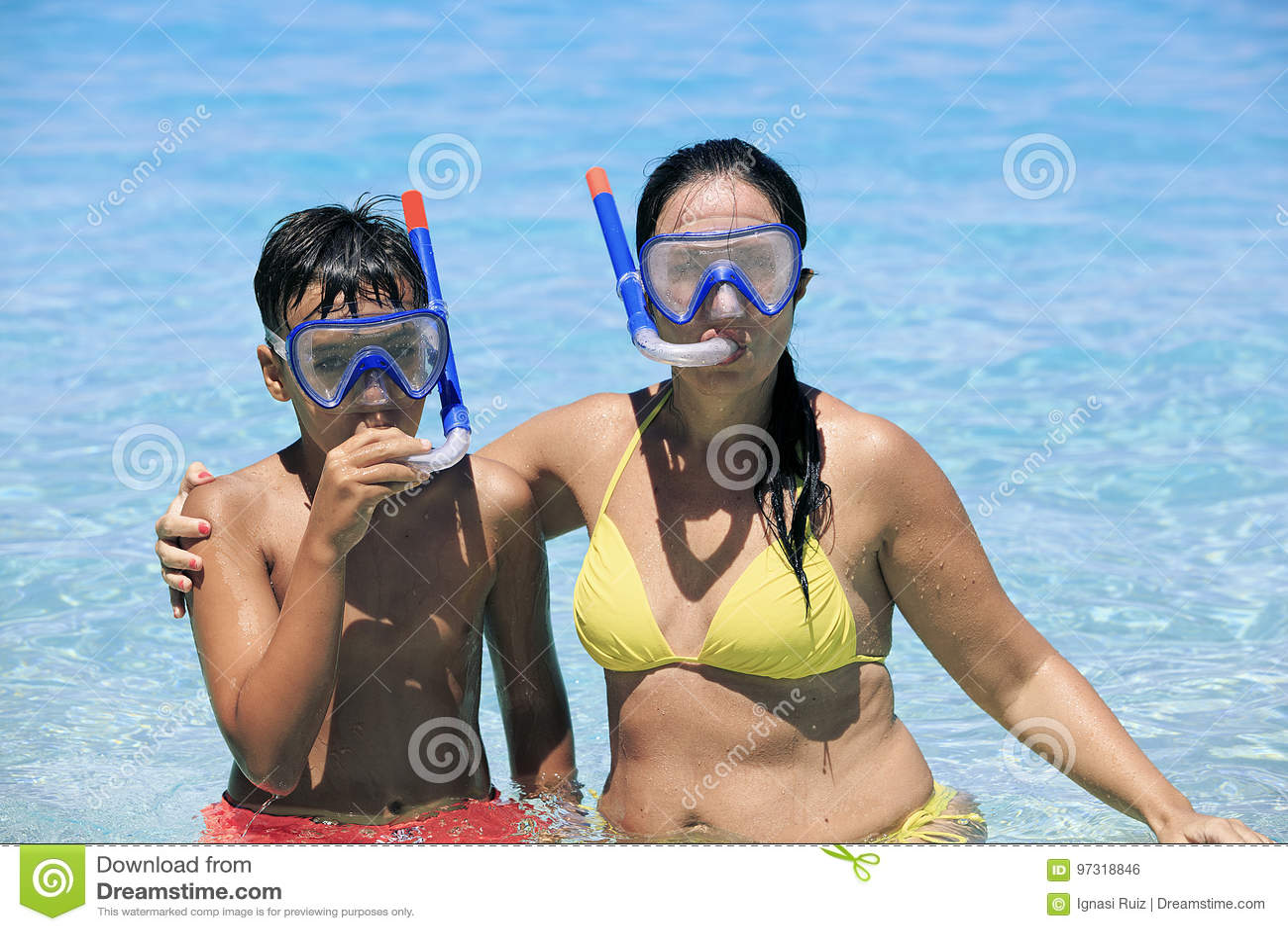 Madre e figlio che si immergono sulla spiaggia