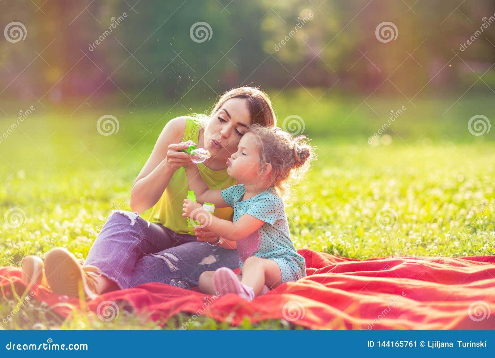 Madre e hija en la espuma de la sopa de los soplos del parque y hacer burbujas