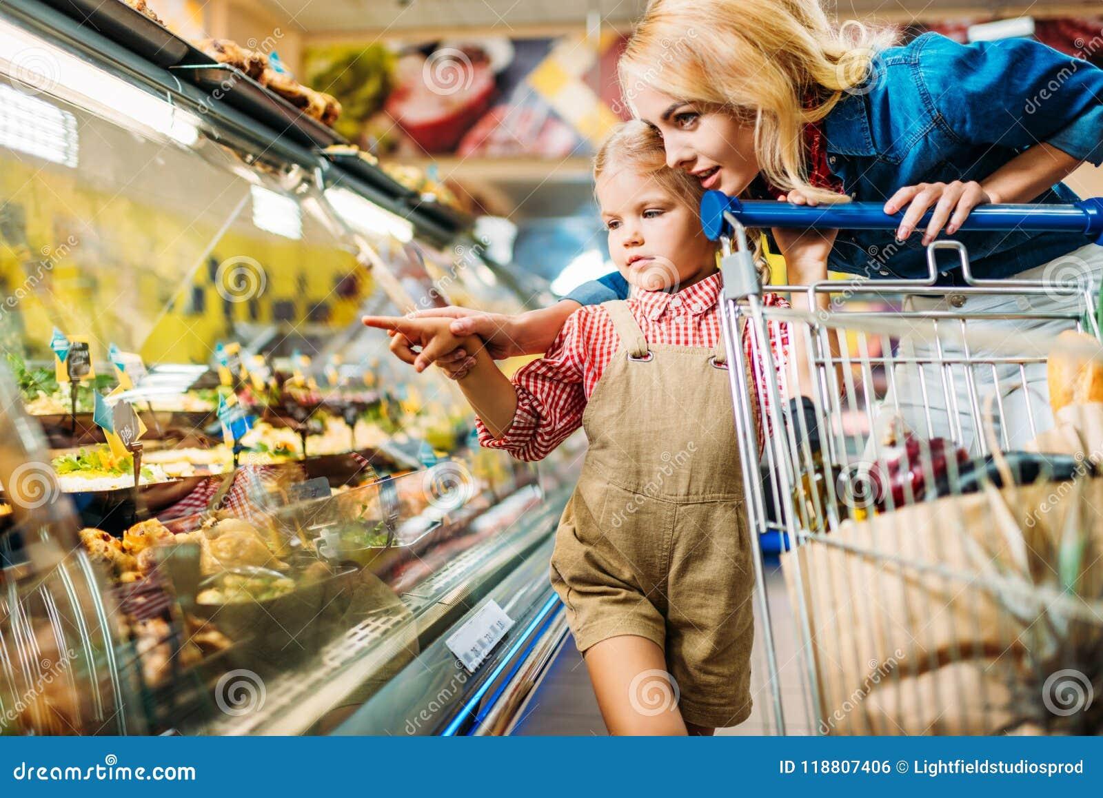 Madre e hija hermosas con la carretilla de las compras que elige la comida mientras que hace compras