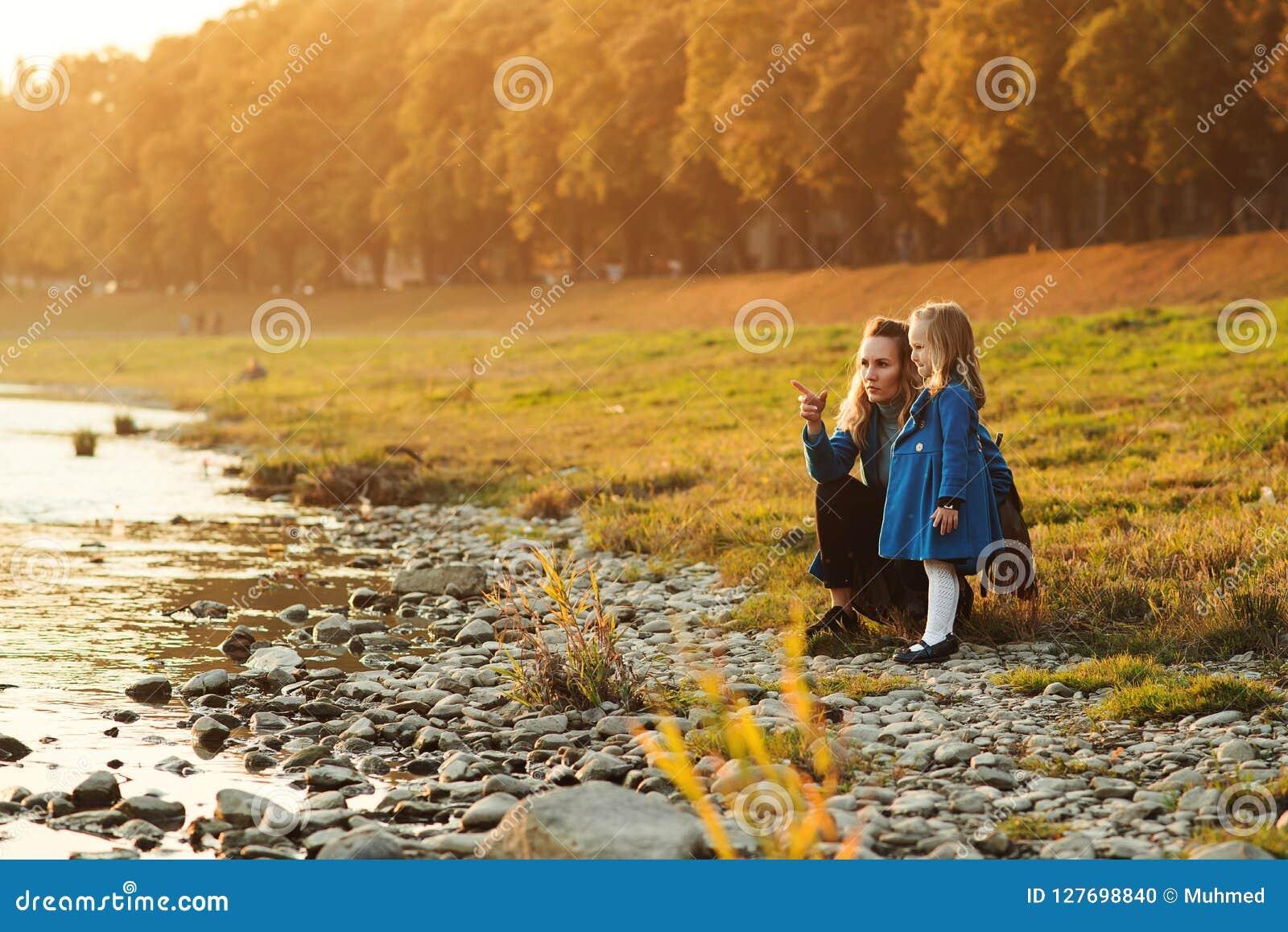 Madre e hija que caminan cerca del río en tiempo del otoño Familia feliz Fin de semana de la caída en el aire abierto Familia que