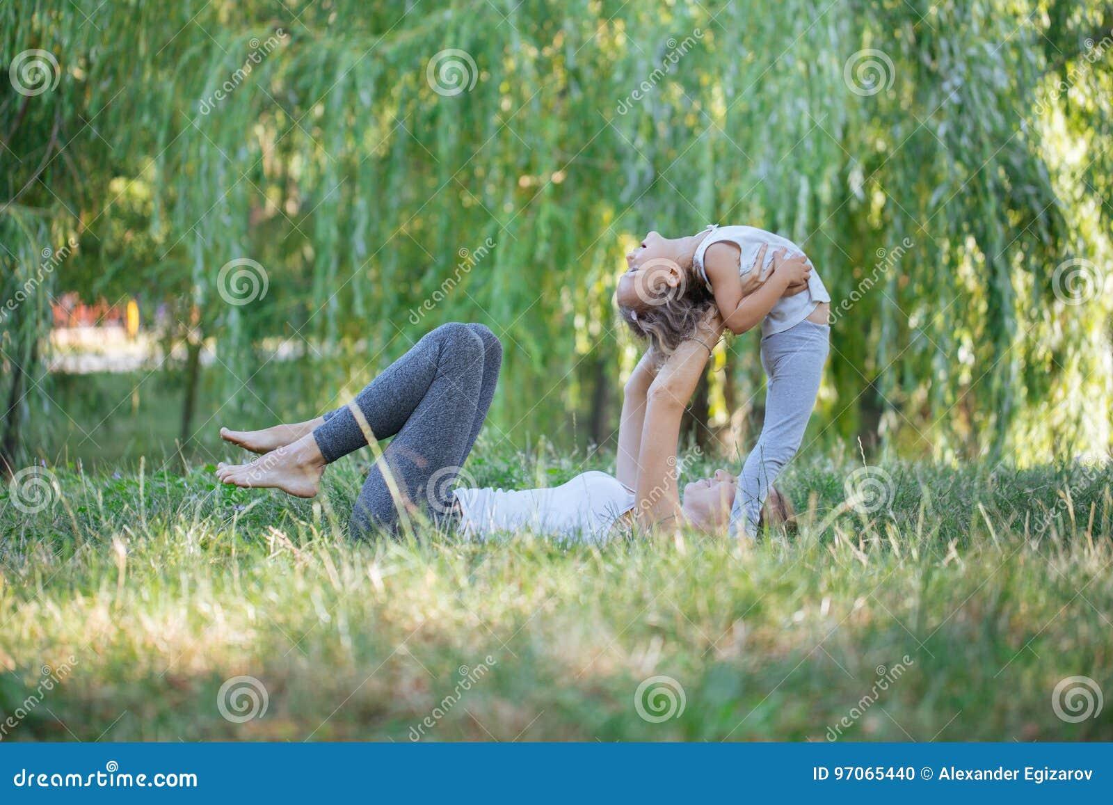 Madre e hija que hacen ejercicios de la yoga en hierba en el parque en el tiempo del día