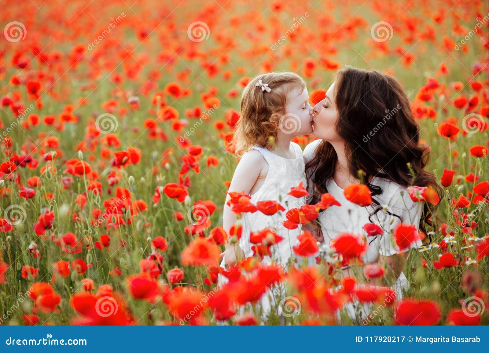 Madre e hija que juegan en campo de flor