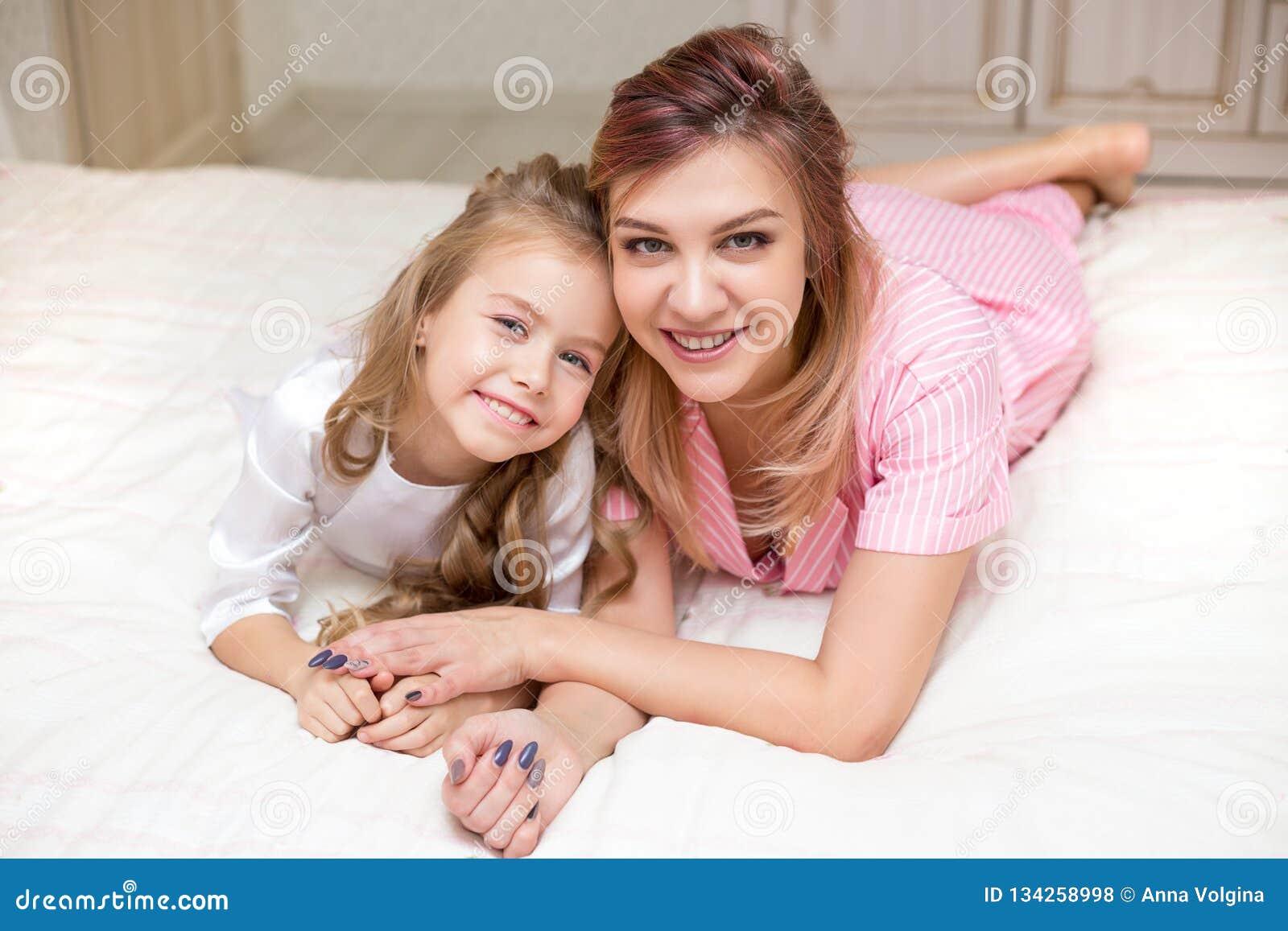 Madre e hija que juegan en una cama junto