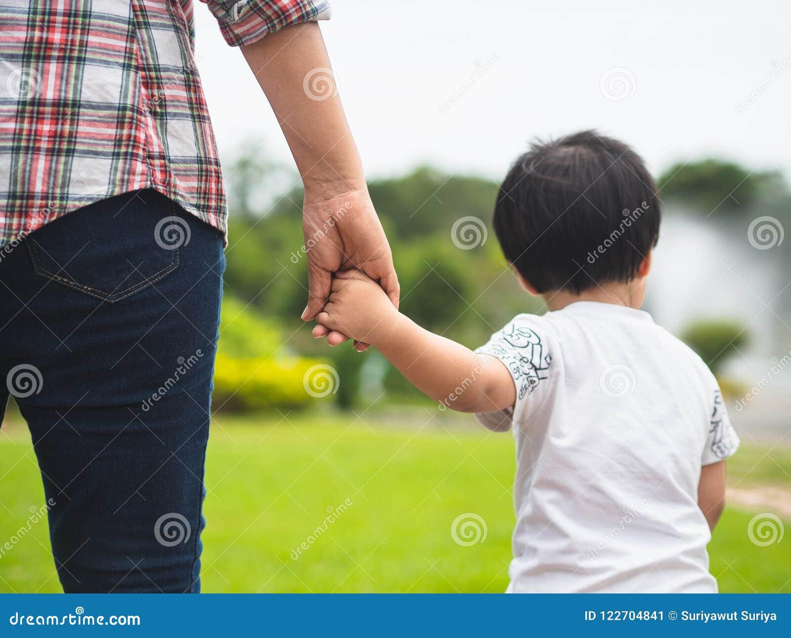 Madre e hija que llevan a cabo las manos que caminan en el parque Niño y M