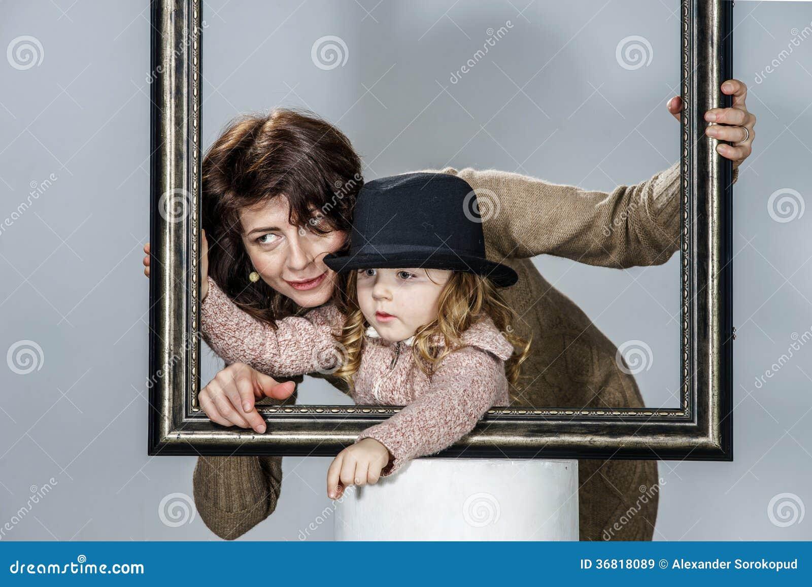 Madre E Hija Que Presentan Con El Marco Imagen de archivo - Imagen ...