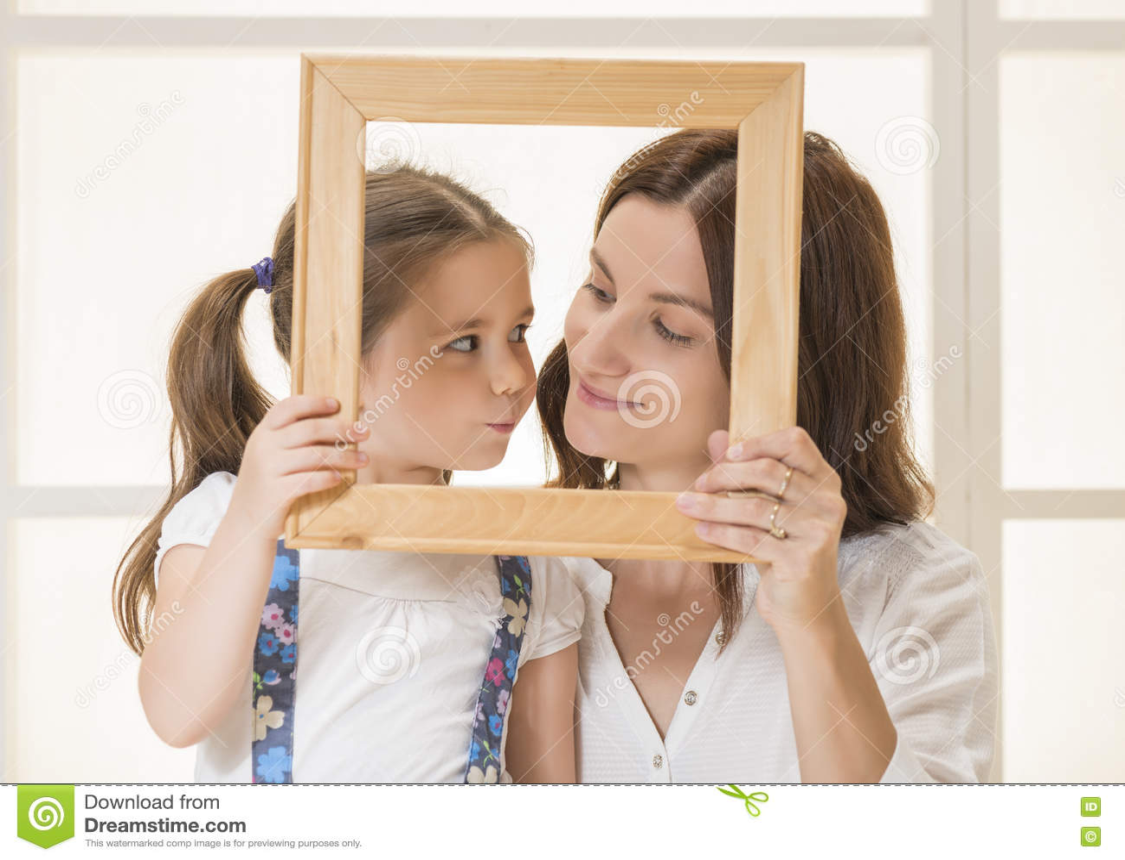 Madre E Hija Que Presentan Con El Marco Foto de archivo - Imagen de ...