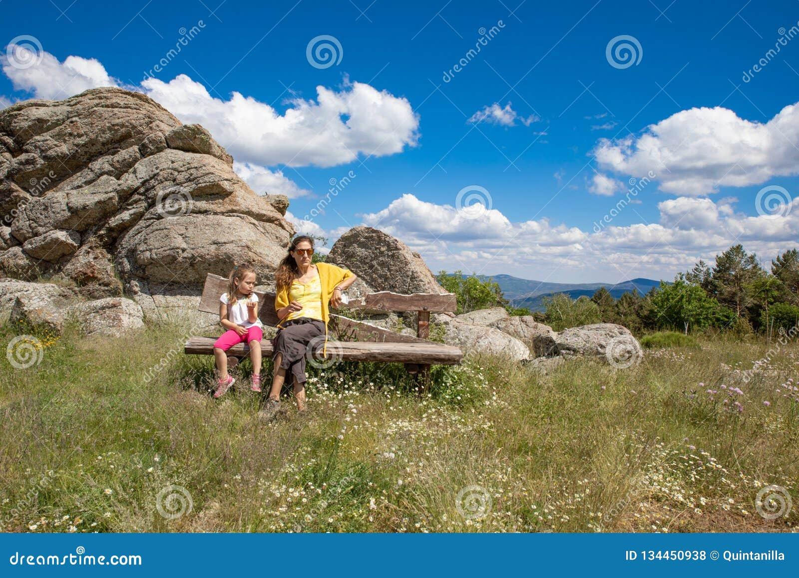 Madre e hija que se sientan en banco de madera en el campo de Madrid