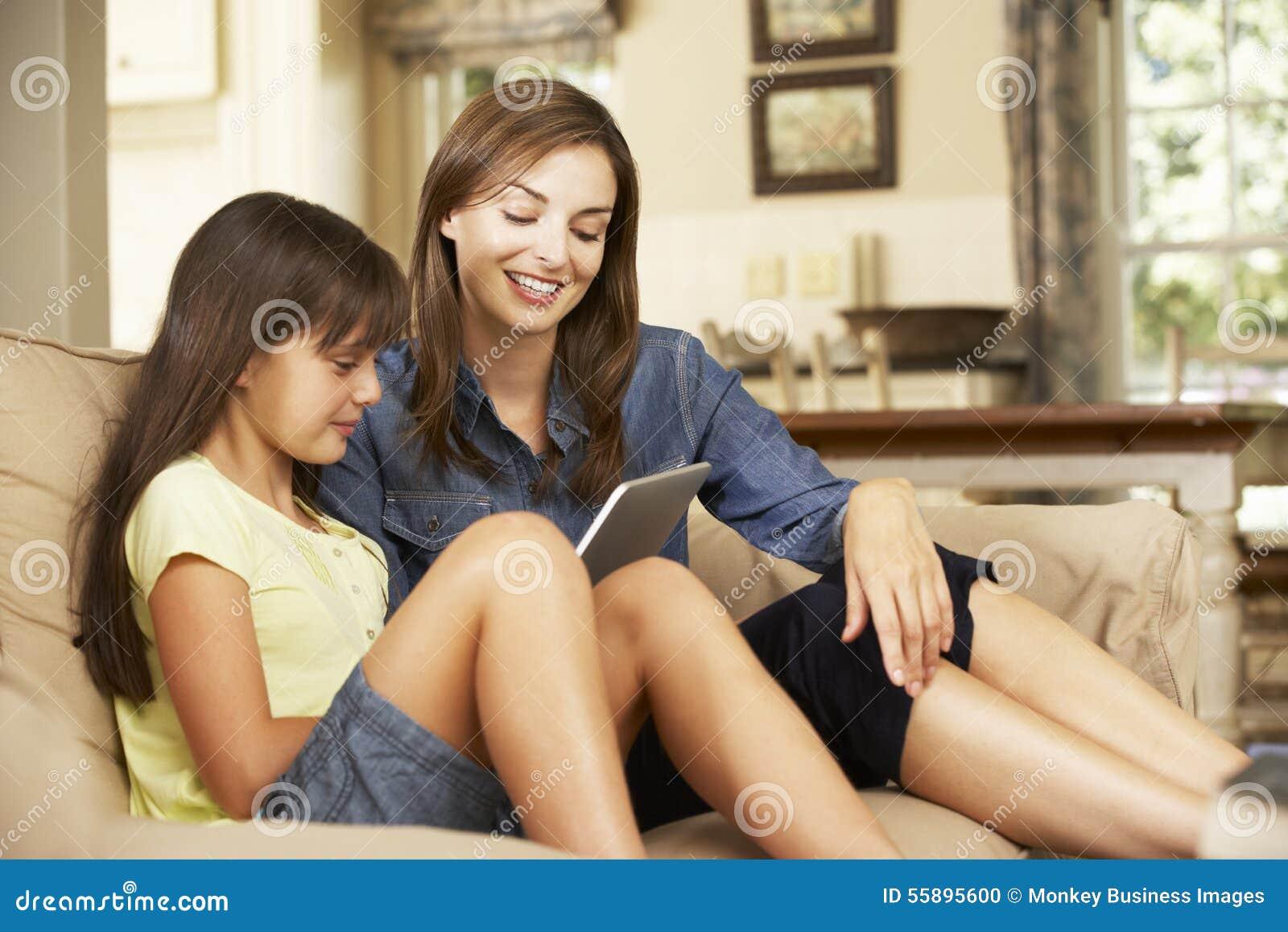 Madre e hija que se sientan en el ordenador de Sofa At Home Using Tablet