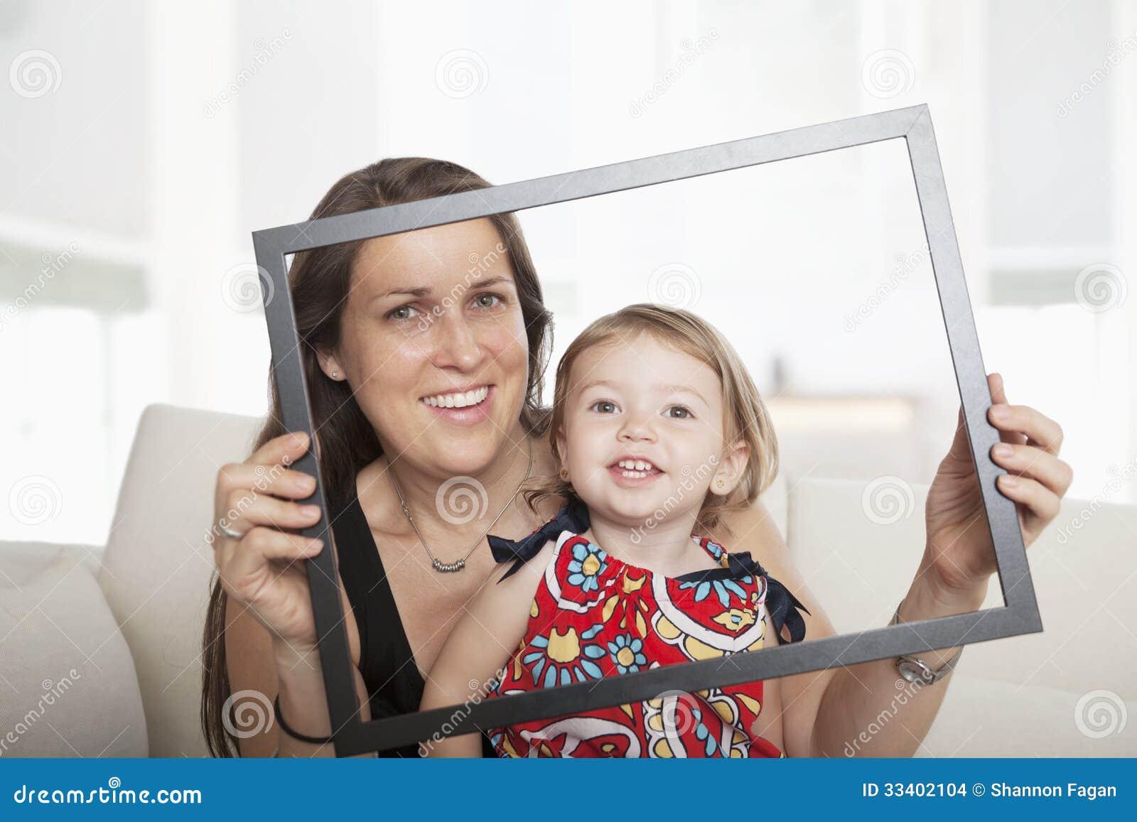 Madre E Hija Que Soportan Un Marco Y Que Miran A Través De él Foto ...