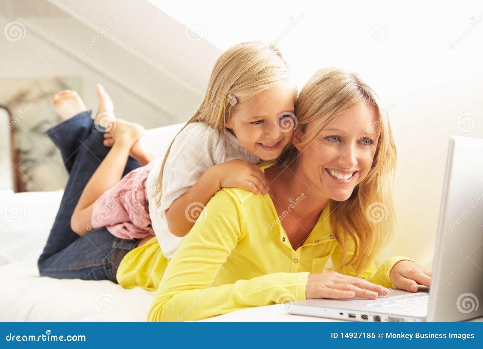 Madre e hija que usa la computadora portátil que se relaja en el sofá