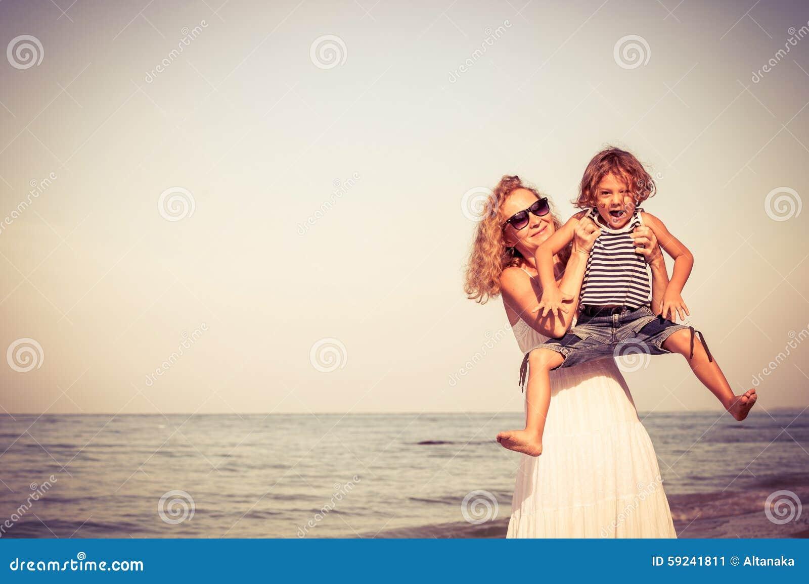 Madre e hijo que juegan en la playa en el tiempo del día