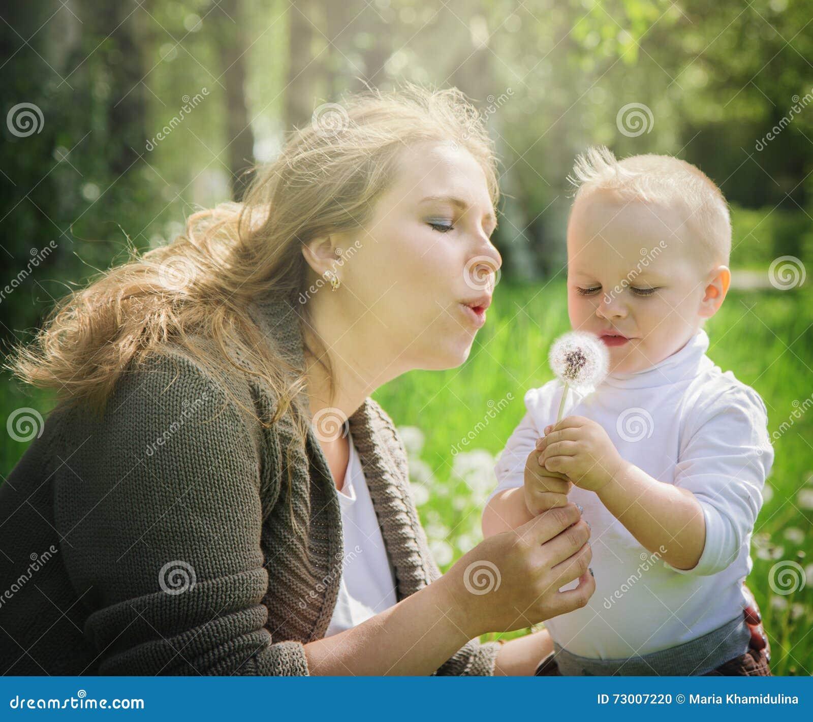 Madre e hijo que soplan en un diente de león