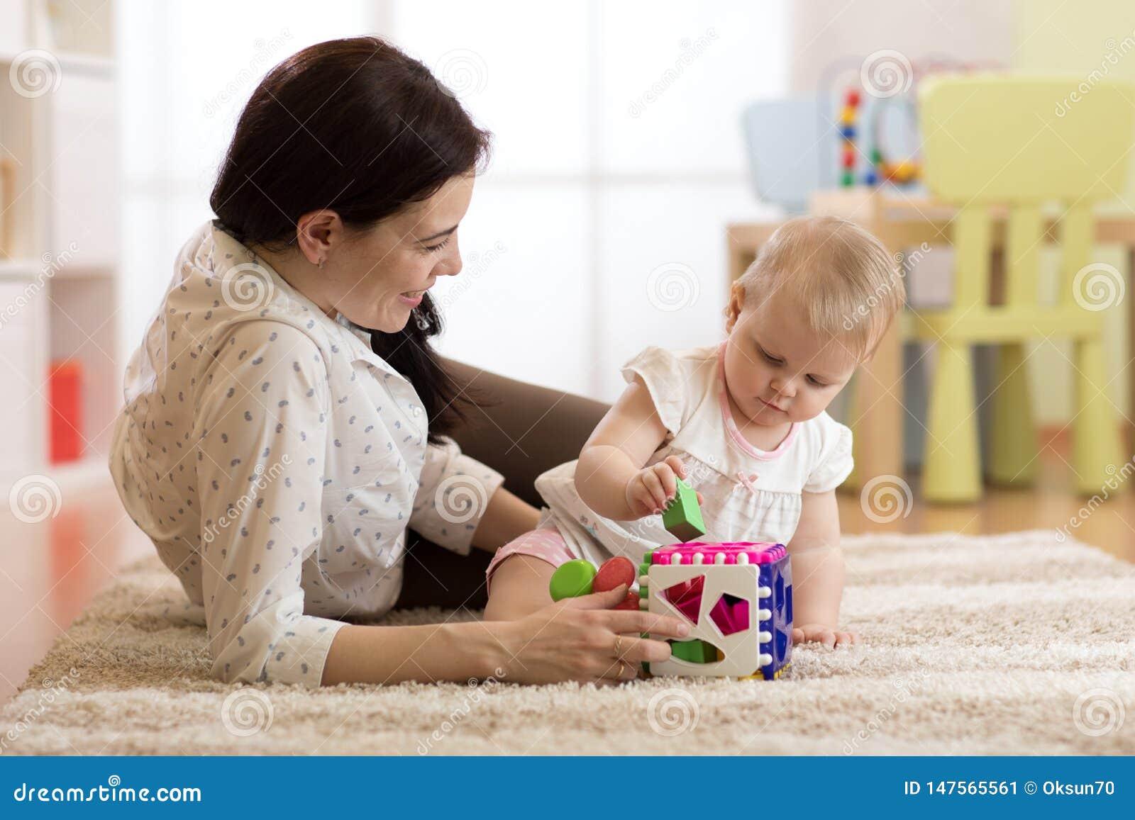 Madre e neonata che giocano con i giocattoli inerenti allo sviluppo nella stanza della scuola materna