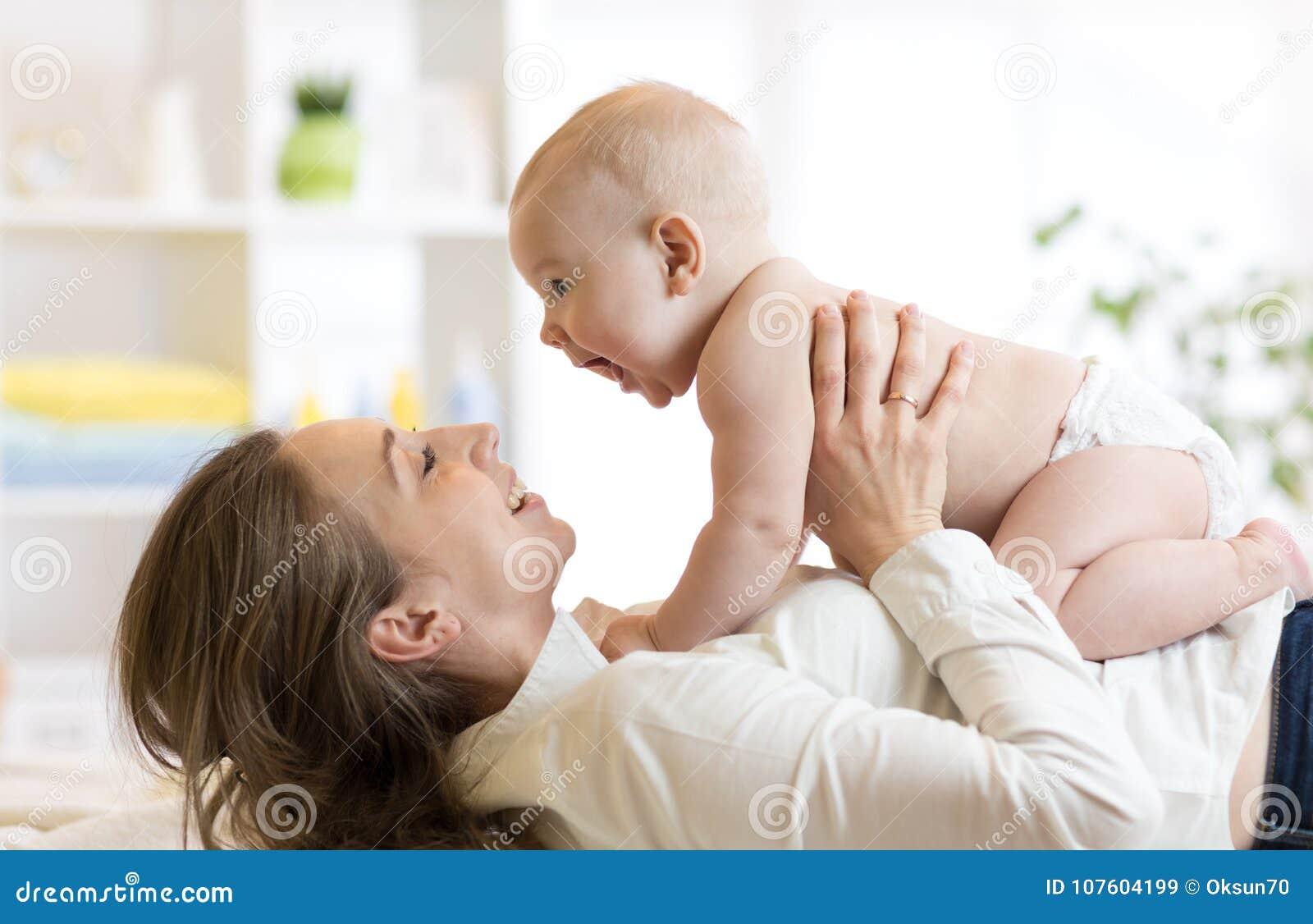 Madre e neonato in pannolino che gioca nella stanza soleggiata Genitore e bambino che si rilassano a casa Famiglia che ha diverti