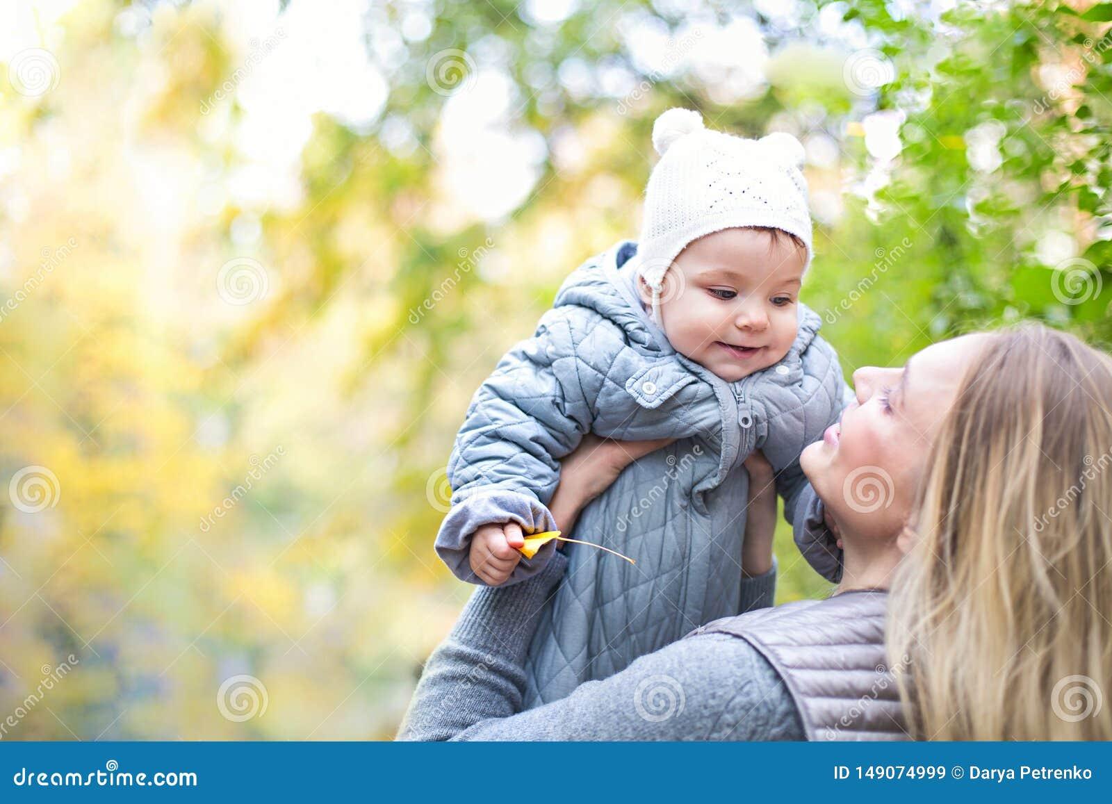 Madre ed il suo piccolo gioco della figlia che stringono a s? sulla passeggiata di autunno in natura all aperto