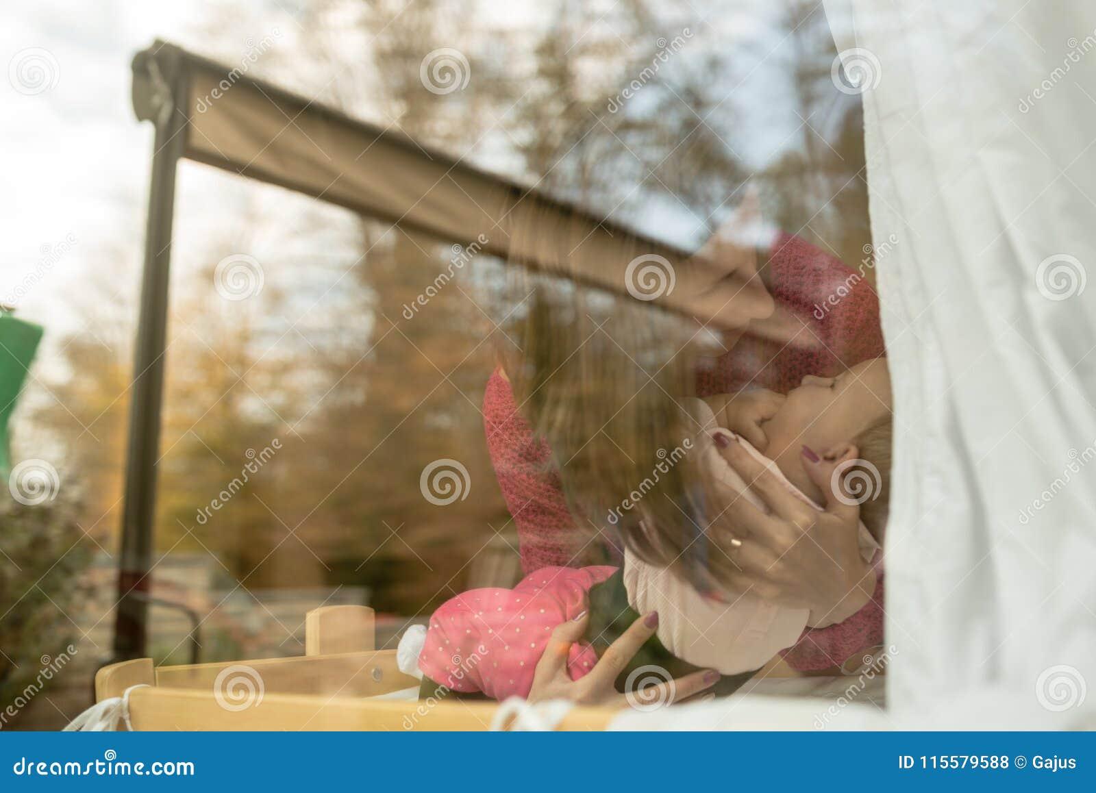 Madre en el jersey rosado que detiene a un bebé dentro en casa