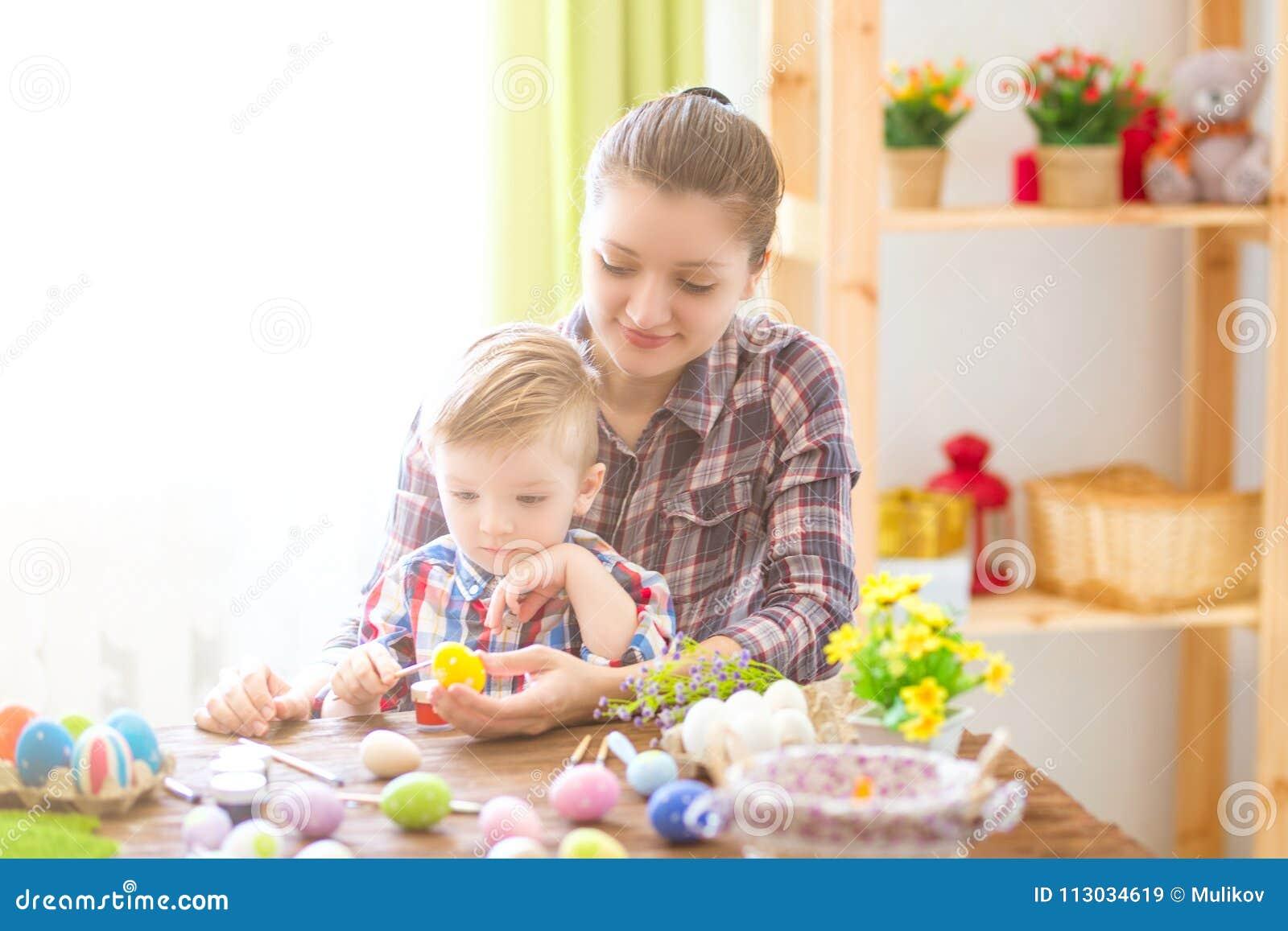 Madre encantadora e hijo que celebran Pascua Familia que celebra Pascua Juego del padre y del niño dentro Adornado a casa y flujo