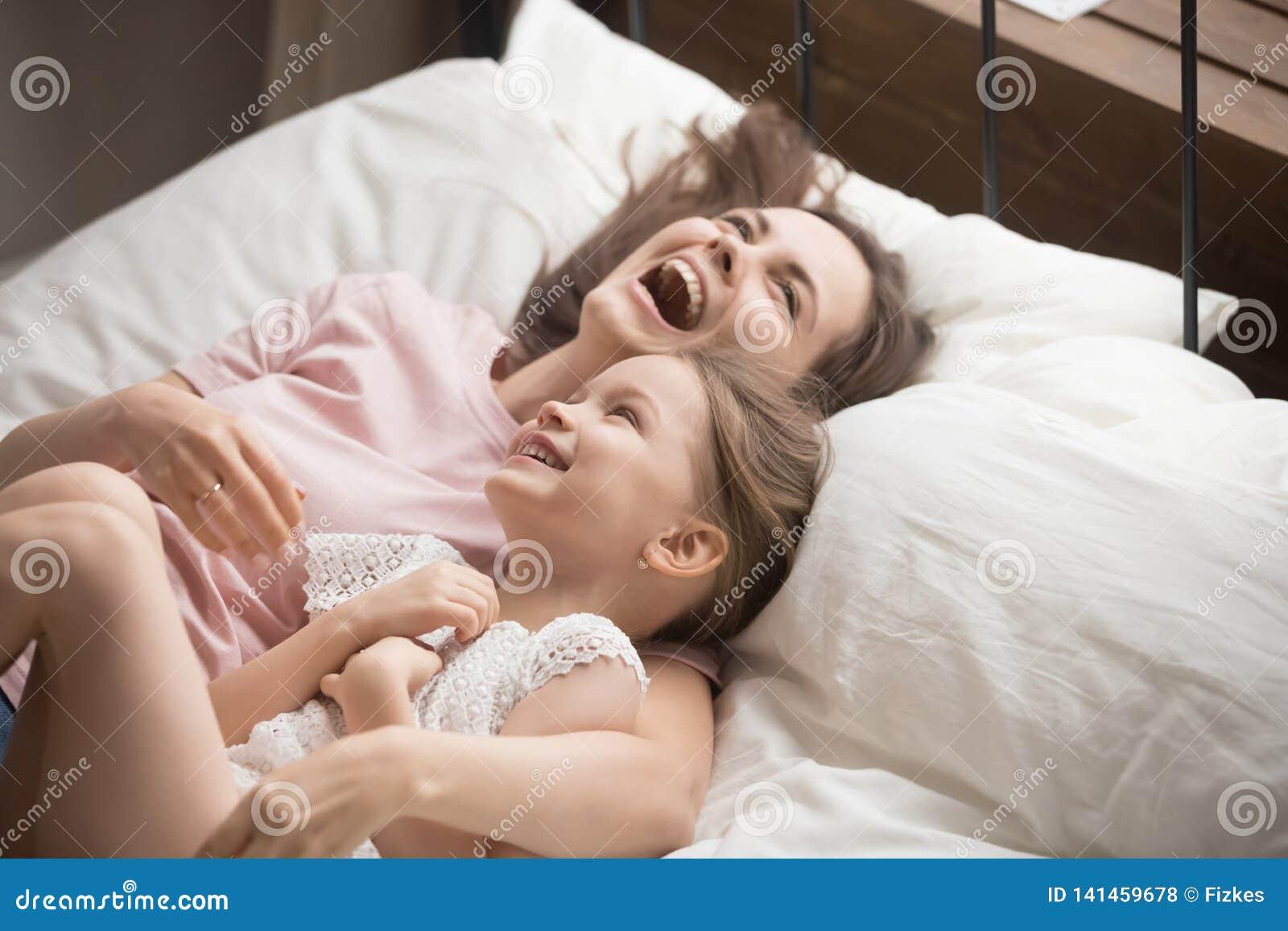 Madre felice della famiglia che abbraccia menzogne di risata della figlia del bambino sul letto