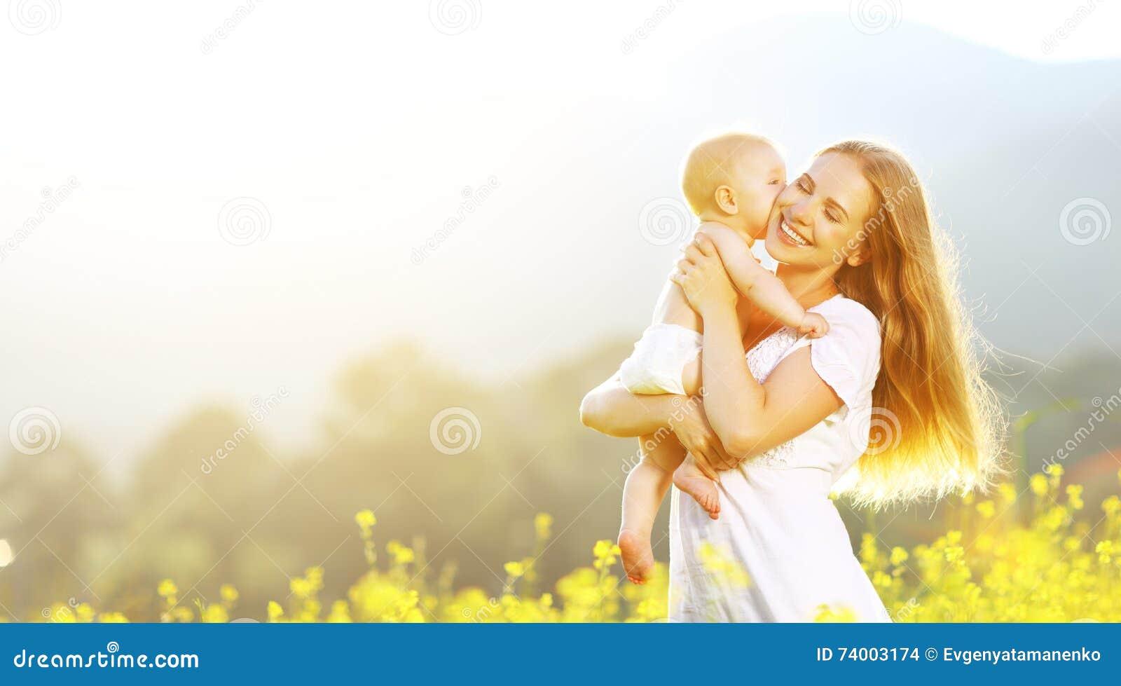 Madre felice della famiglia ed abbracciare e bacio del bambino di estate su natur