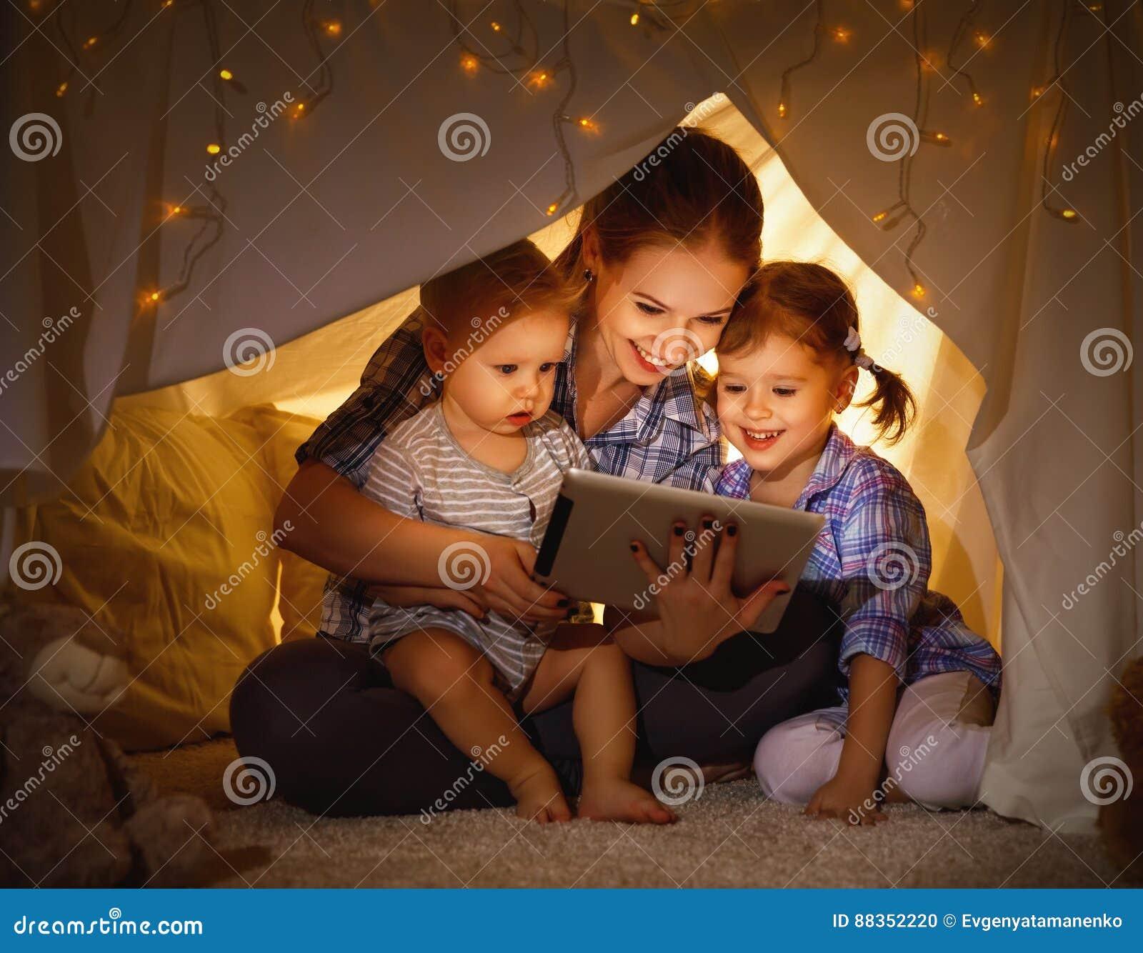 Madre felice e bambini della famiglia che giocano in pc della compressa