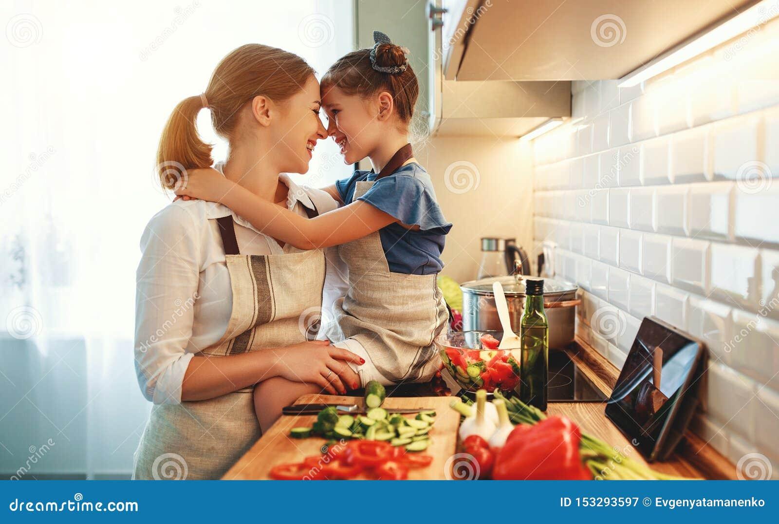 Madre feliz de la familia con la muchacha del ni?o que prepara la ensalada vegetal